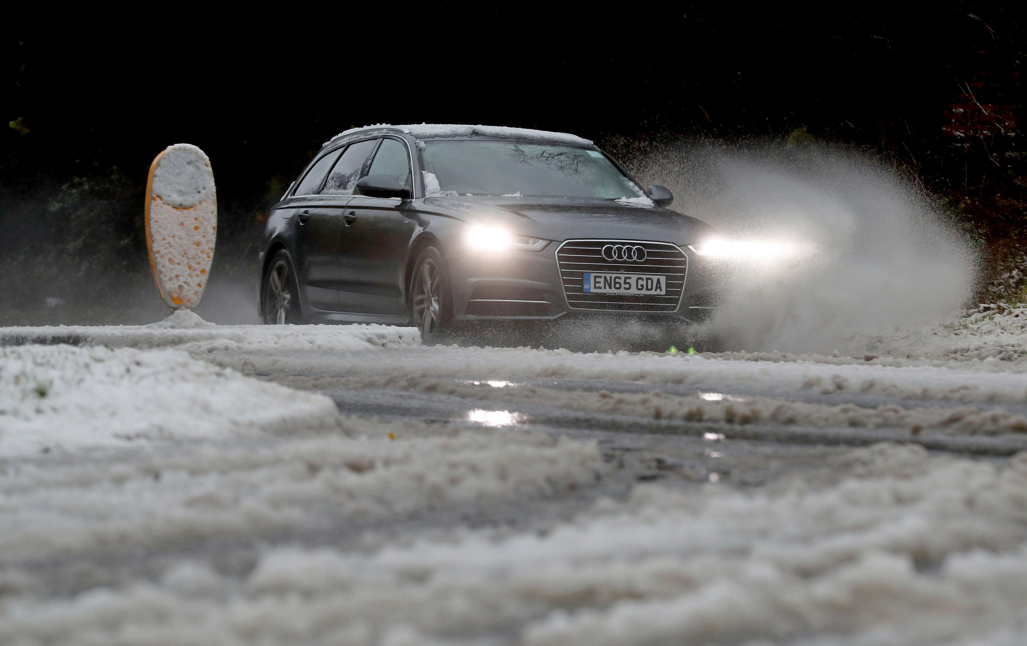 A car negotiates its way through hazardous road conditions in Canterbury, England, after heavy snow fell across parts of the UK, Sunday Dec. 10, 2017.  Snow and freezing weather is causing travel disruptions across central England and northern Wales, grounding some flights and shutting down roads. (Gareth Fuller/PA via AP)