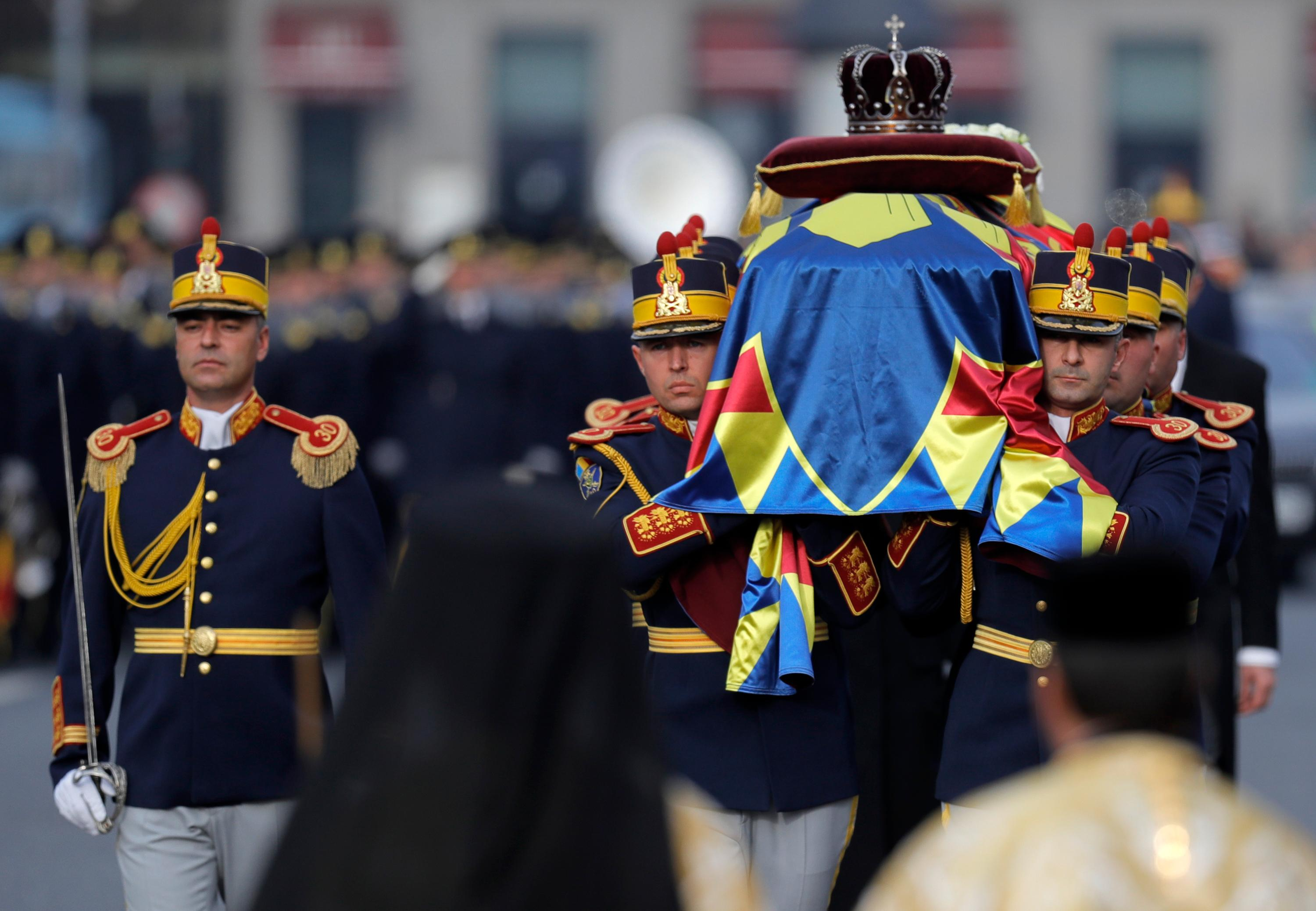Honor guard soldiers carry the coffin of the late Romanian King Michael during the funeral ceremony outside the former royal palace in Bucharest, Romania, Saturday, Dec.16, 2017. Thousands waited in line to pay their respects to Former King Michael, who ruled Romania during WWII, and died on Dec. 5, 2017, aged 96, in Switzerland. (AP Photo/Vadim Ghirda)