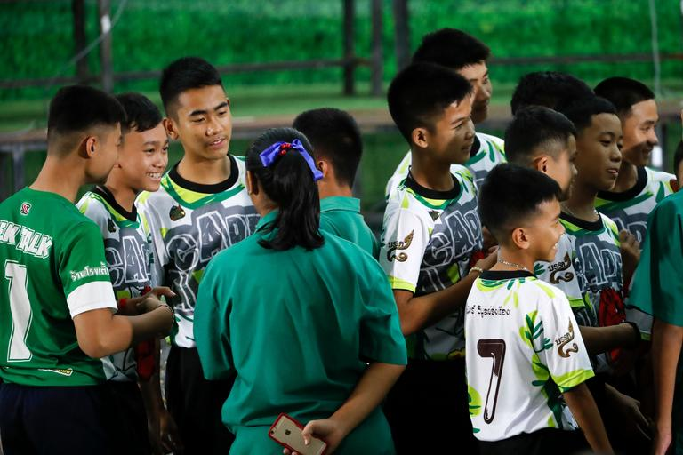 Members of the rescued soccer team and their coach are greeted by their friends before a press conference discussing their experience of being trapped a flooded cave in Chiang Rai, northern Thailand, Wednesday, July 18, 2018. The 12 boys and their soccer coach rescued after being trapped in a flooded cave in northern Thailand are recovering well and are eager to eat their favorite comfort foods after their expected to go home soon. (AP Photo/Vincent Thian)