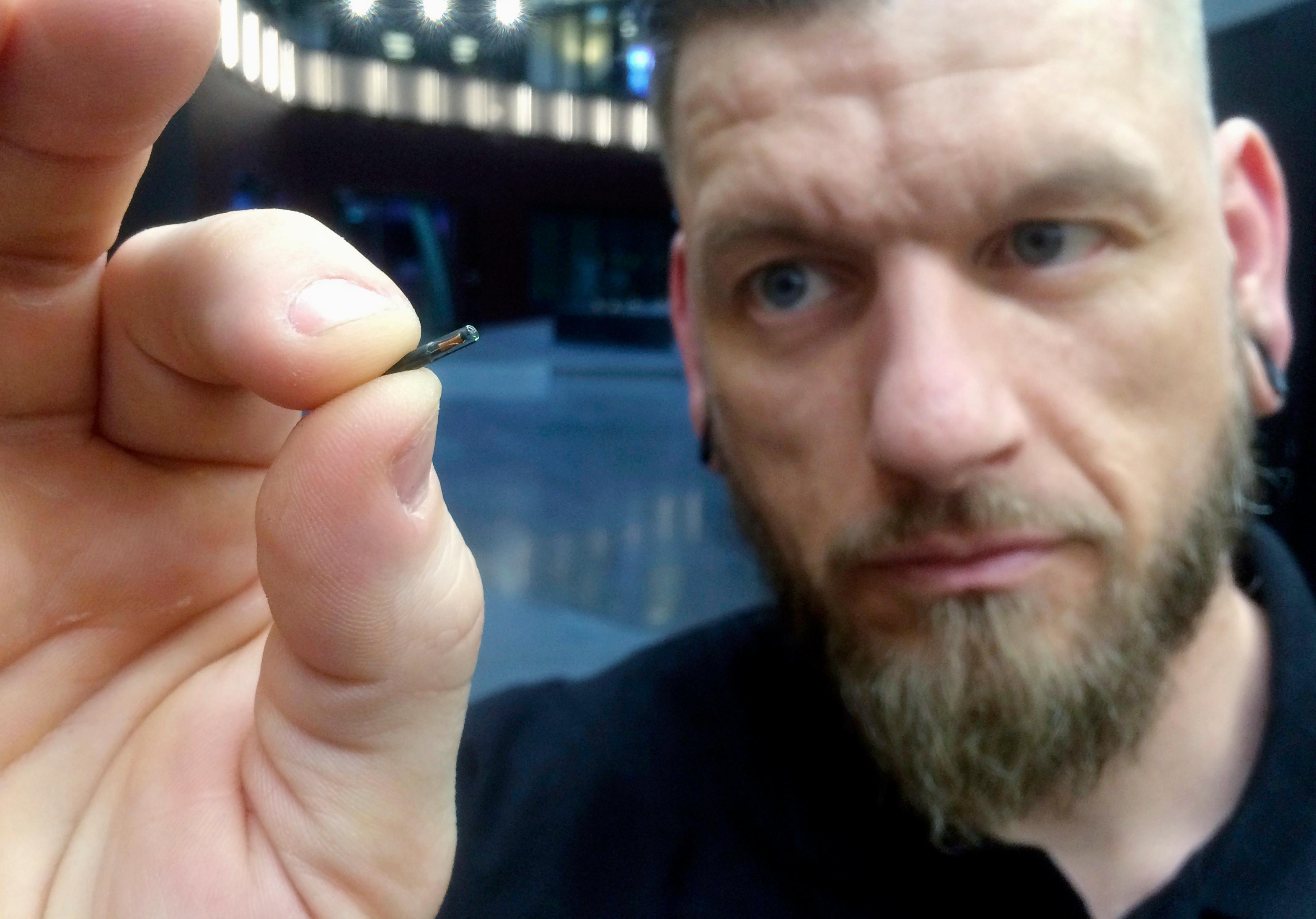 FILE - In this March 14, 2017, file photo, Jowan Osterlund from Biohax Sweden, holds a small microchip implant, similar to those implanted into workers at the Epicenter digital innovation business center during a party at the co-working space in central Stockholm. (AP Photo/James Brooks, File)