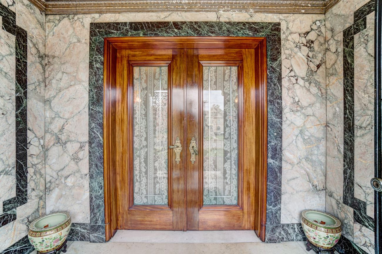 Gorgeous wood doors framed by marble welcome you into the home. / Image: Adam Sanregret courtesy of Coldwell Banker West Shell // Published: 4.3.20
