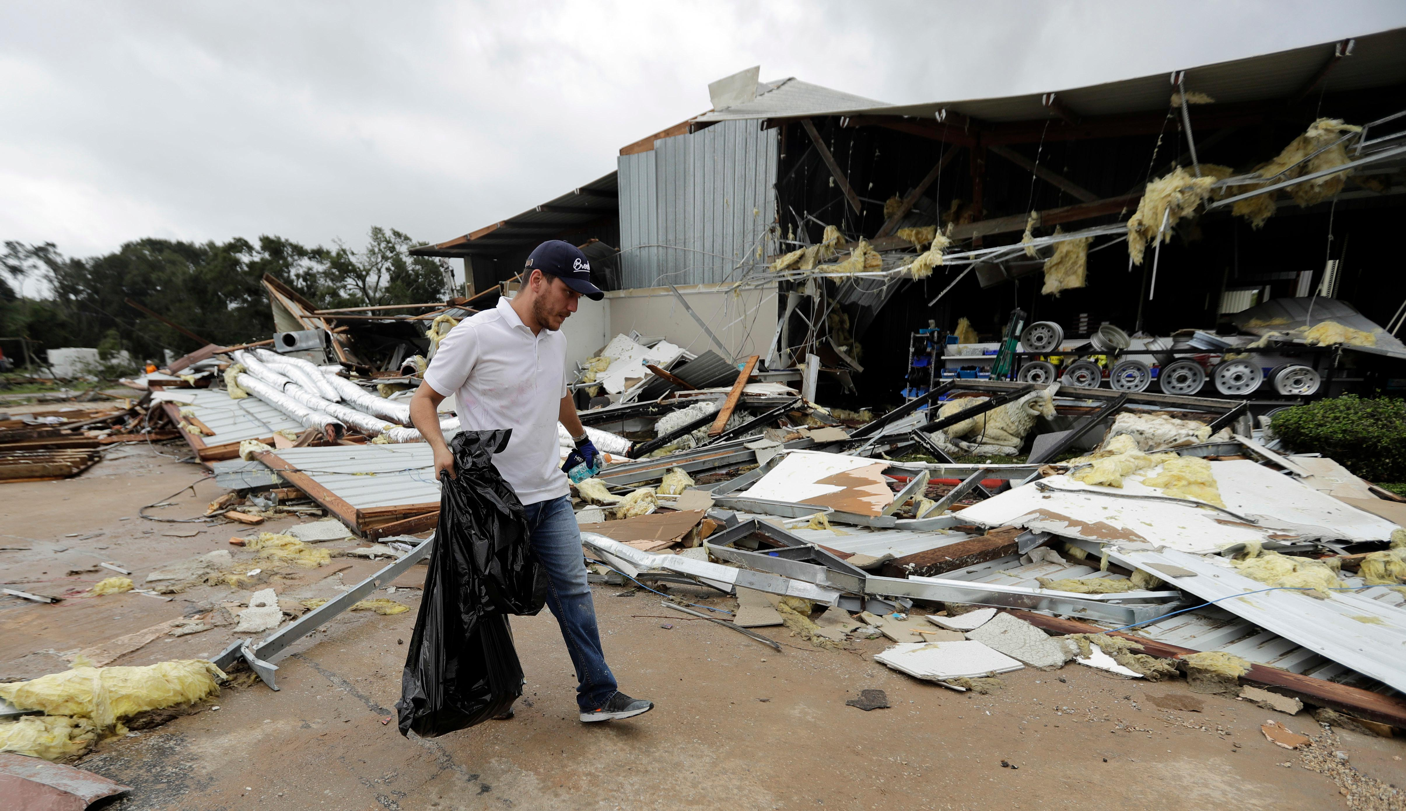 Miguel Debernardis cleans up debris in the aftermath of Hurricane Harvey Saturday, Aug. 26, 2017, in Katy, Texas.   Harvey rolled over the Texas Gulf Coast on Saturday, smashing homes and businesses and lashing the shore with wind and rain so intense that drivers were forced off the road because they could not see in front of them. (AP Photo/David J. Phillip)