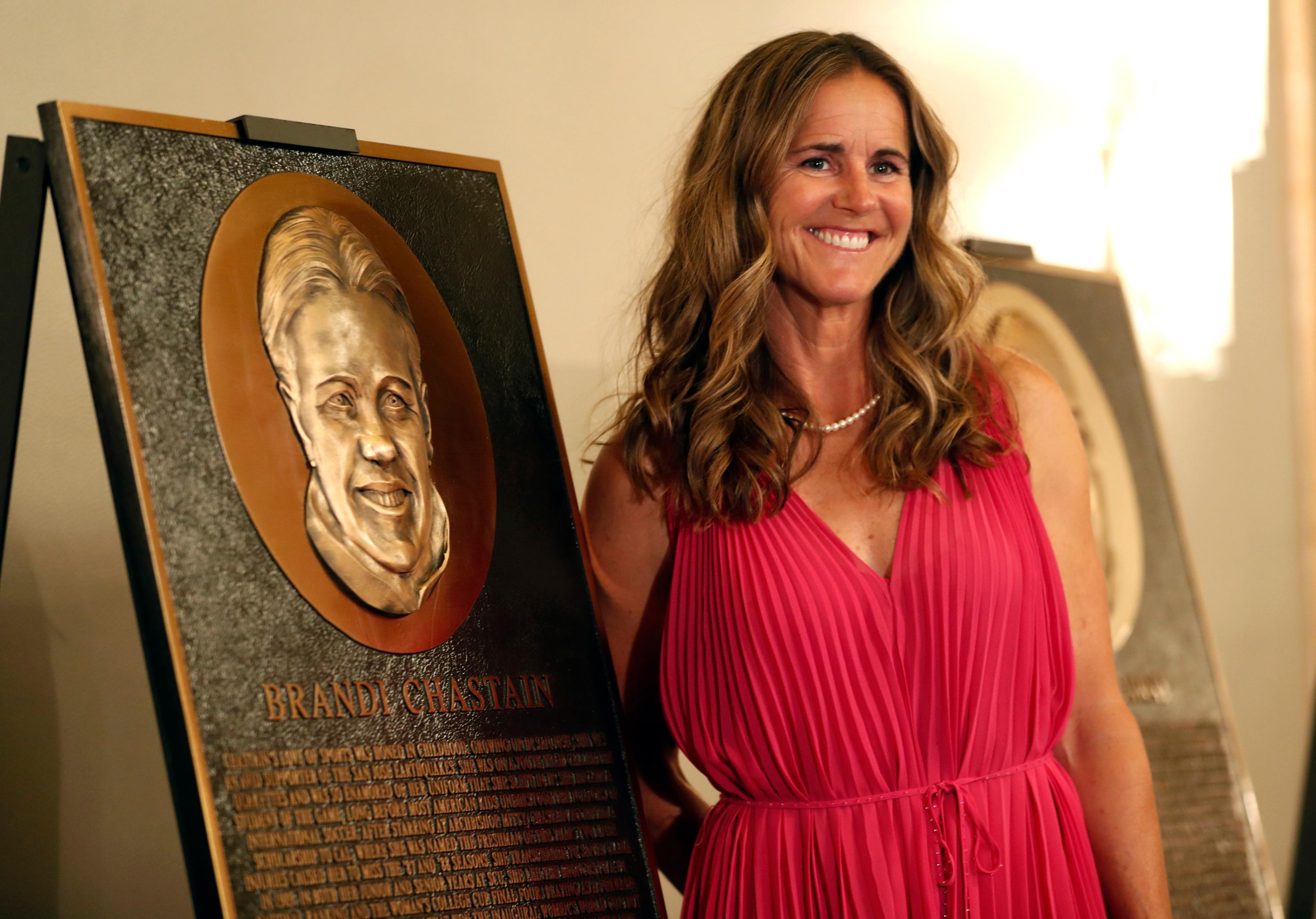 "In this photo taken Monday May 21, 2018, Bay Area Sports Hall of Hame inductee Brandi Chastain poses by her plaque during a press conference in San Francisco. Social media is finding little to like about the likeness on a plaque honoring retired soccer champion Chastain. The Bay Area Sports Hall of Fame in San Francisco unveiled the plaque on Monday night. Chastain diplomatically said ""it's not the most flattering. But it's nice."" (Scott Strazzante/San Francisco Chronicle via AP)"