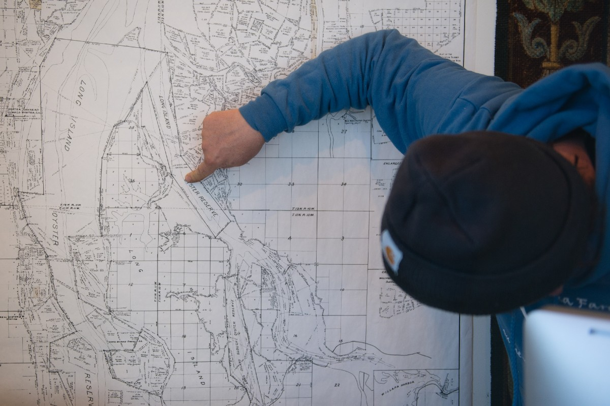 Dan Driscoll pointing out his key spots on a detailed map of the area. (Image: Chona Kasinger / Seattle Refined)