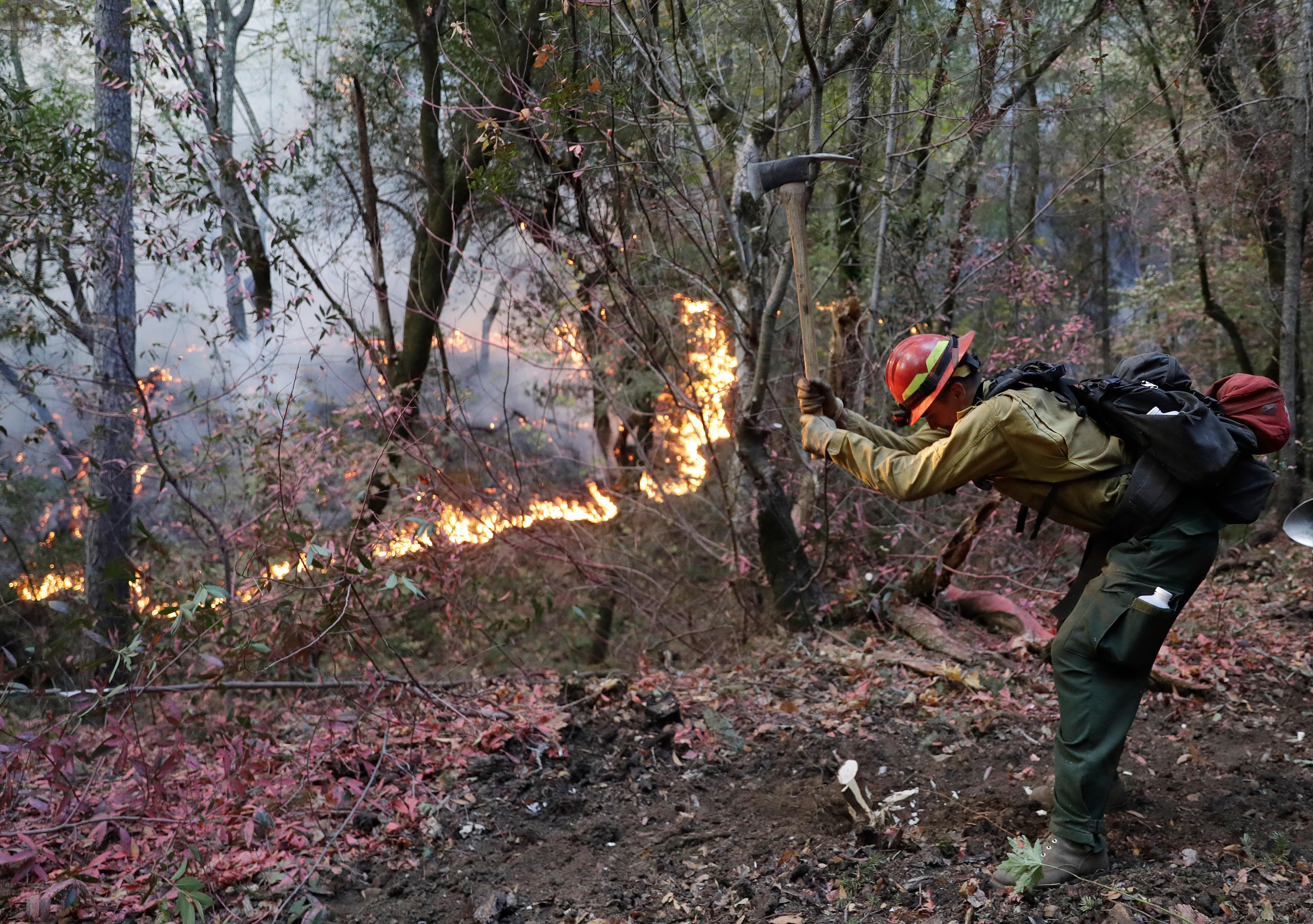 A firefighter cuts fuel from an advancing wildfire Saturday, Oct. 14, 2017, in Santa Rosa, Calif. (AP Photo/Marcio Jose Sanchez)