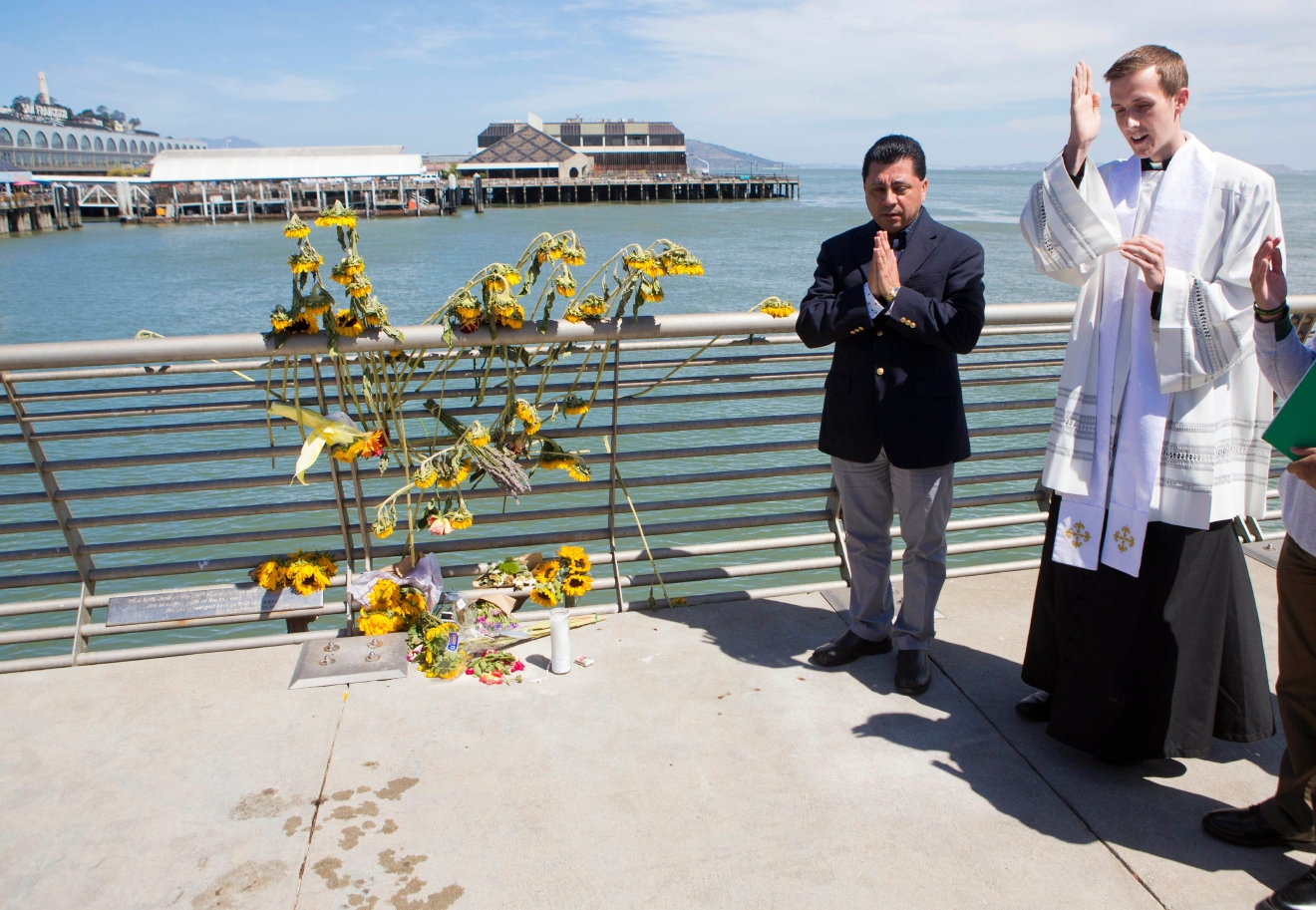 FILE - In this July 6, 2015 file photo, Father Cameron Faller, right, and Julio Escobar, of Restorative Justice Ministry, conduct a vigil for Kathryn Steinle on Pier 14 in San Francisco. (AP Photo/Beck Diefenbach, File)<p></p>
