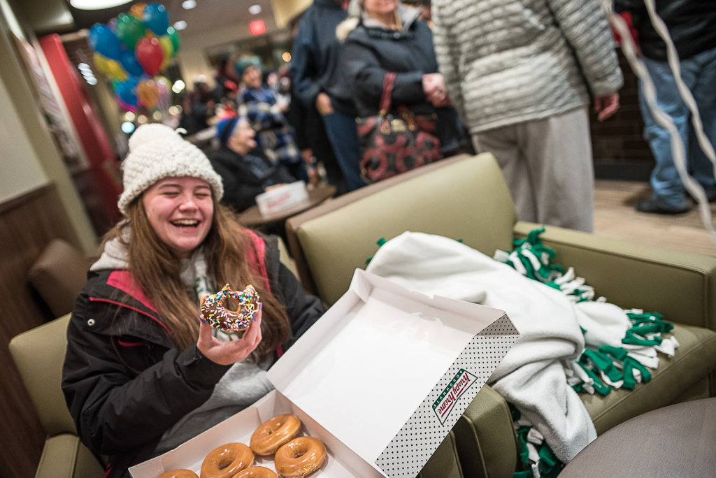 Paige Maheux enjoys her first Krispy Kreme doughnut from the new Auburn store. Maheux and a couple of her friends waited outside the store for it to open for 12 hours. (Andree Kehn/Sun Journal)