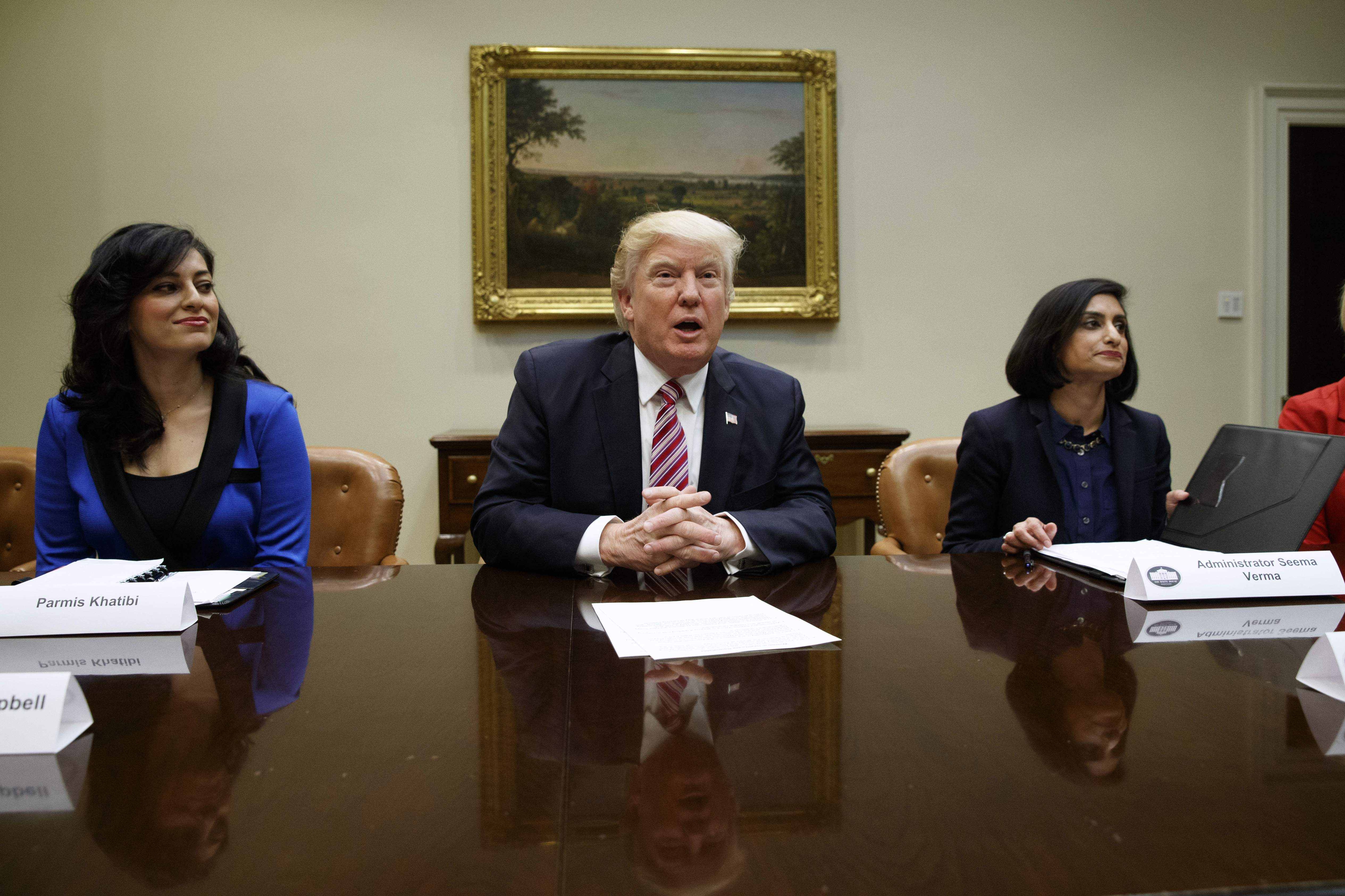 DAY 62 - In this March 22, 2017, file photo, President Donald Trump speaks during a meeting on women in healthcare in the Roosevelt Room of the White House in Washington. From left are, Parmis Khatibi, Trump, and administrator of the Centers for Medicare and Medicaid Services Seema Verma. (AP Photo/Evan Vucci, File)