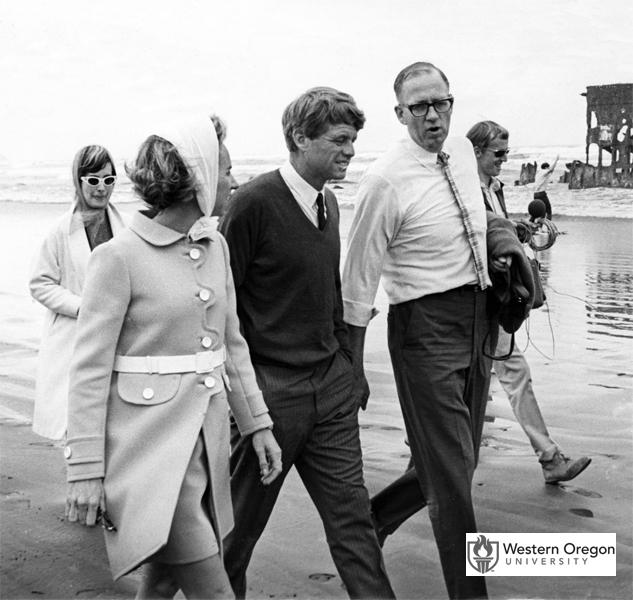 Senator Robert F. Kennedy, wife Ethel Kennedy, and Oregon State Treasurer Robert W. Straub walk together on the beach near Fort Stevens State Park. In the background are the remains of the Peter Iredale shipwreck. The photo was taken during Kennedy's visit before the 1968 Oregon primary election shortly before his assassination. (Western Oregon University Archives - Robert W. Straub Collection/Used with permission)