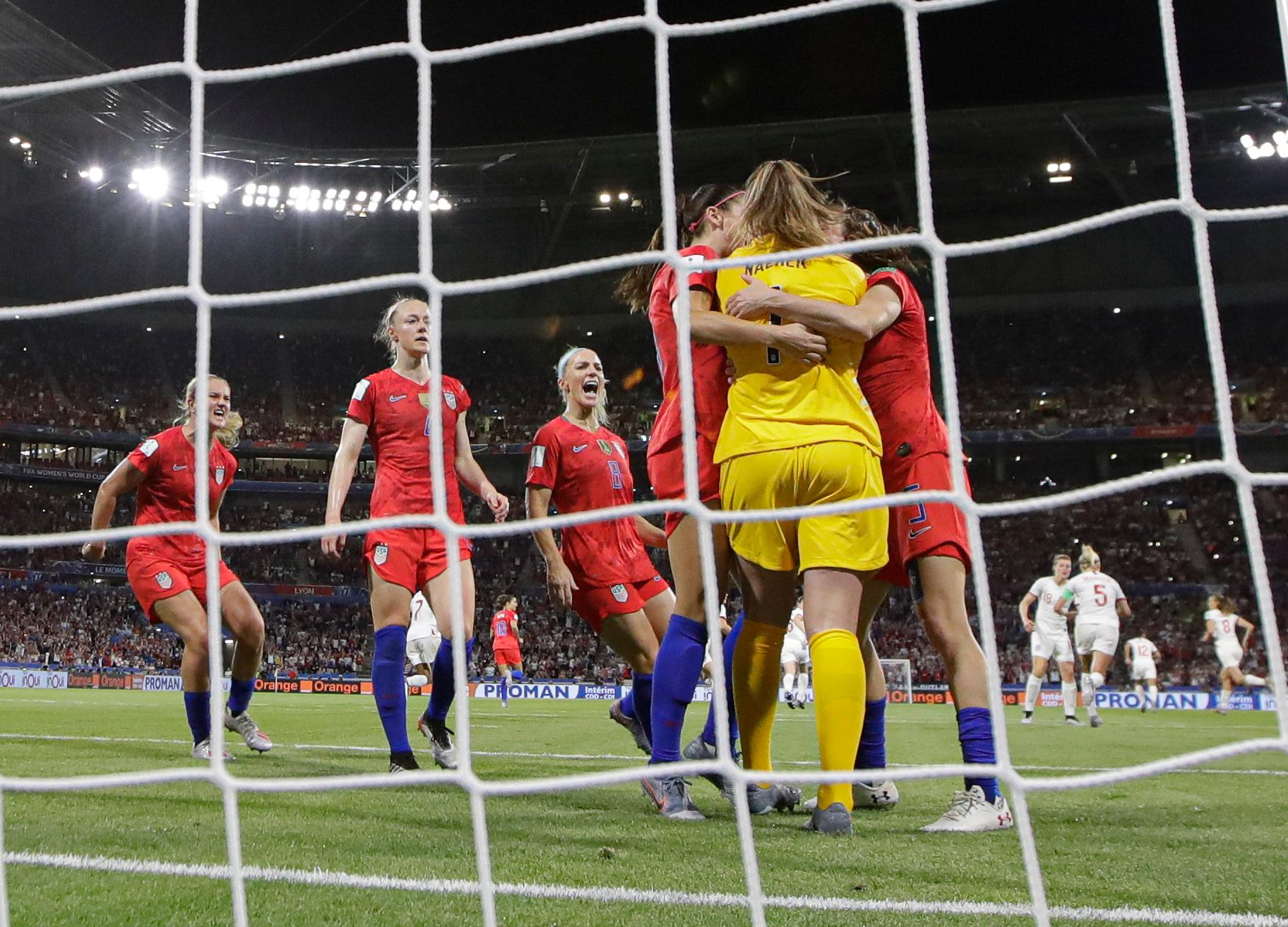 Team mates hug United States goalkeeper Alyssa Naeher after she saved a penalty shot taken by England's Steph Houghton during the Women's World Cup semifinal soccer match between England and the United States, at the Stade de Lyon, outside Lyon, France, Tuesday, July 2, 2019. (AP Photo/Alessandra Tarantino)