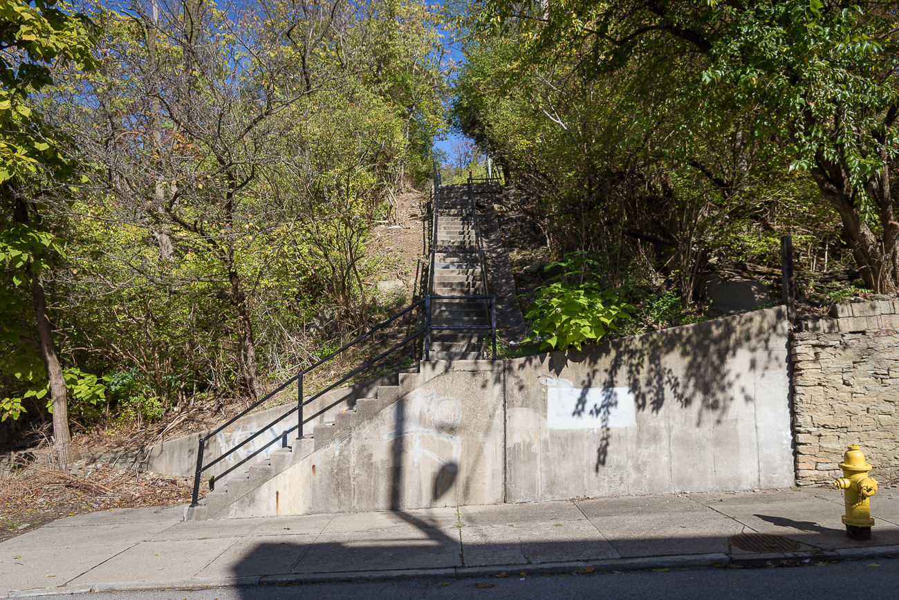 The Main Street Steps, the longest public staircase in Cincinnati, spans roughly 890 feet from base to summit. They connect Mulberry Street (where Main Street begins/ends) in Over-the-Rhine to Eleanor Place by Jackson Hill Park in Mt. Auburn. The stairs follow the path of the former Mt. Auburn Incline, which quickly brought trolleys from OTR up to the top of the hill. The incline closed in 1898 and stairs were eventually added along the route to resume moving people easily between the two neighborhoods. Today, it still serves as a shortcut between the two places and offers beautiful views through the trees along the climb. / Image: Phil Armstrong, Cincinnati Refined // Published: 11.2.17