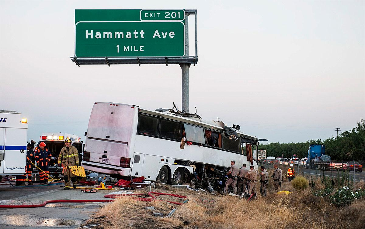 Rescue crews work at the scene of a charter bus crash on northbound Highway 99 between Atwater and Livingston, Calif., Tuesday, Aug. 2, 2016. The bus veered off the central California freeway before dawn Tuesday and struck a pole that sliced the vehicle nearly in half, authorities said. (Andrew Kuhn/Merced Sun-Star via AP)