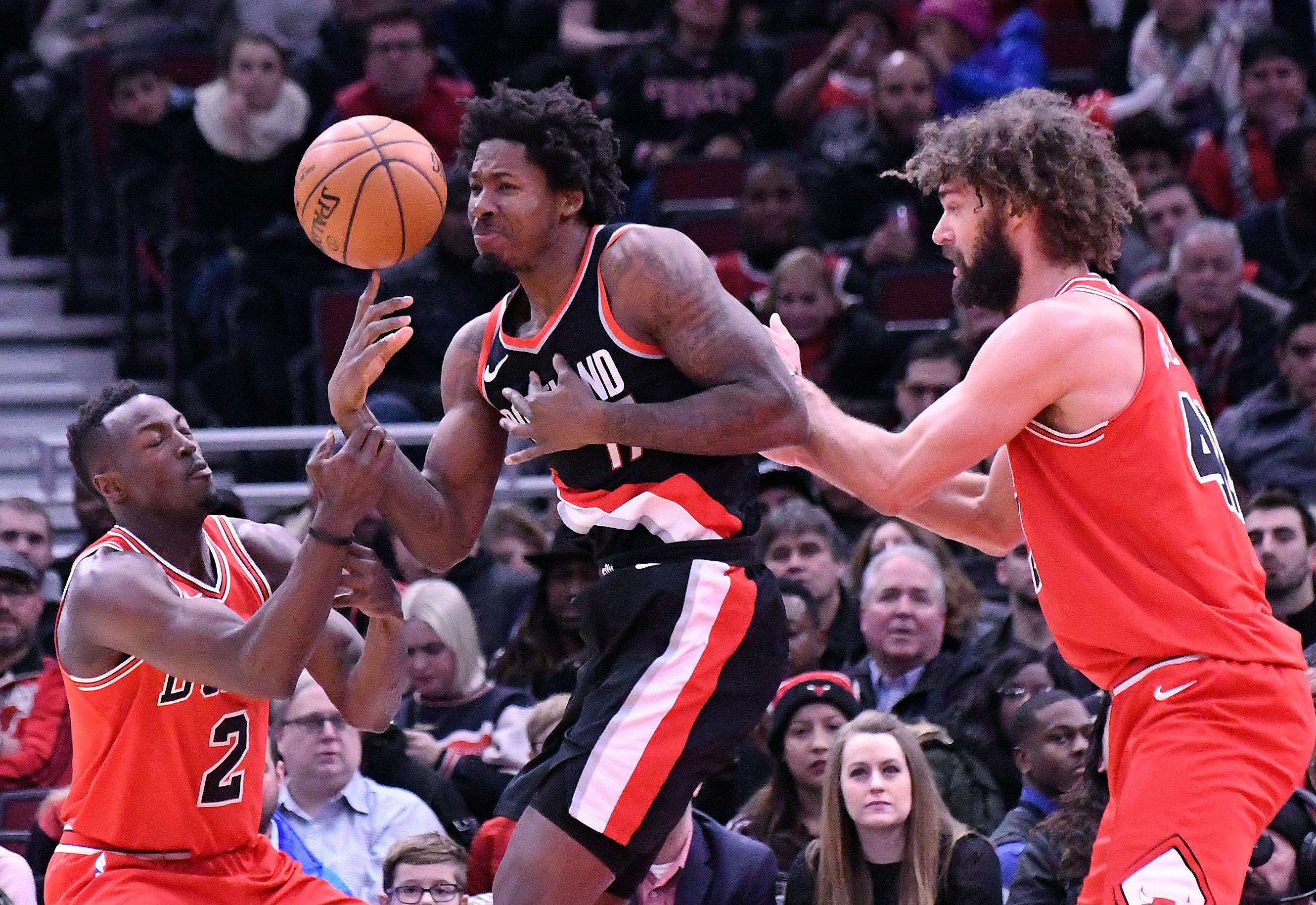 Portland Trail Blazers forward Ed Davis, center, Chicago Bulls guard Jerian Grant, left, and center Robin Lopez, right, go for a loose ball during the first half of an NBA basketball game, Monday, Jan. 1, 2018, in Chicago. (AP Photo/David Banks)