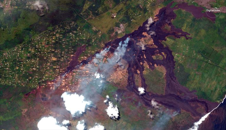 This May 23, 2018, Satellite photo provided by DigitalGlobe shows lava coming out of fissures caused by Kilauea volcano, running towards the Puna coast, lower right, along Malama Ki Forest Reserve recreation area in Pahoa, Hawaii. Puna Geothermal Venture, a geothermal energy plant is seen at upper middle. The Leilani Estates neighborhood, where the volcano has been gushing lava on the big island of Hawaii for the past three weeks, is seen at center left part. (Satellite Image ©2018 DigitalGlobe, a Maxar company via AP)
