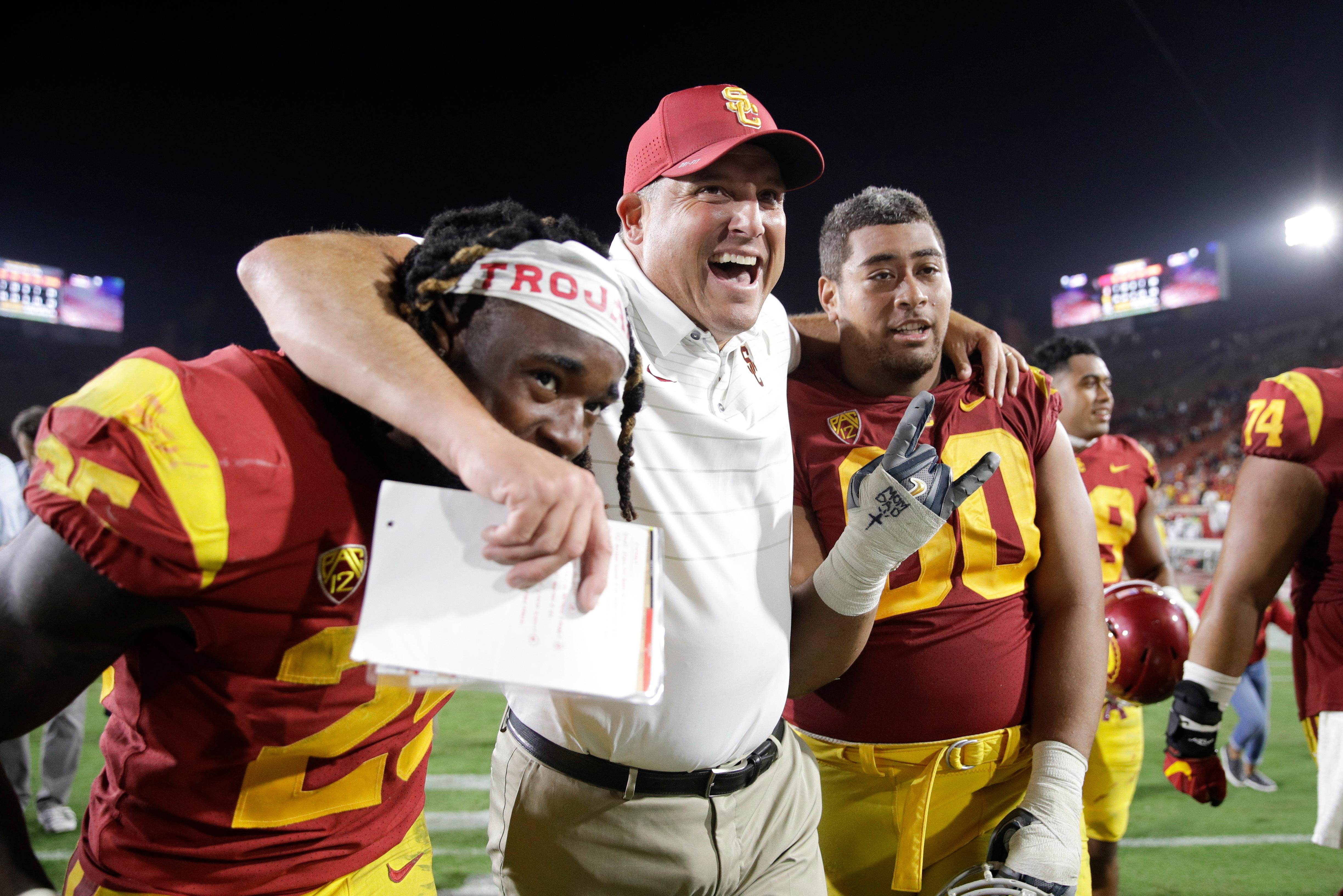 FILE - In this Sept. 9, 2017, file photo, Southern California coach Clay Helton, center, Ronald Jones II, left, and Viane Talamaivao celebrate the team's 42-24 win against Stanford, as they walk off the field after an NCAA college football game in Los Angeles. Helton was selected Pac-12 Coach of the Year, Thursday, Dec. 7, 2017. (AP Photo/Jae C. Hong, File)