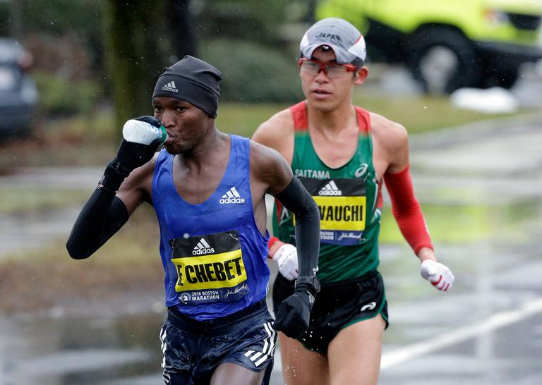 Evans Chebet, of Kenya, leads Yuki Kawauchi, of Japan, as the men's elite field of runners compete in the 122nd Boston Marathon on Monday, April 16, 2018, in Ashland, Mass. (AP Photo/Steven Senne)