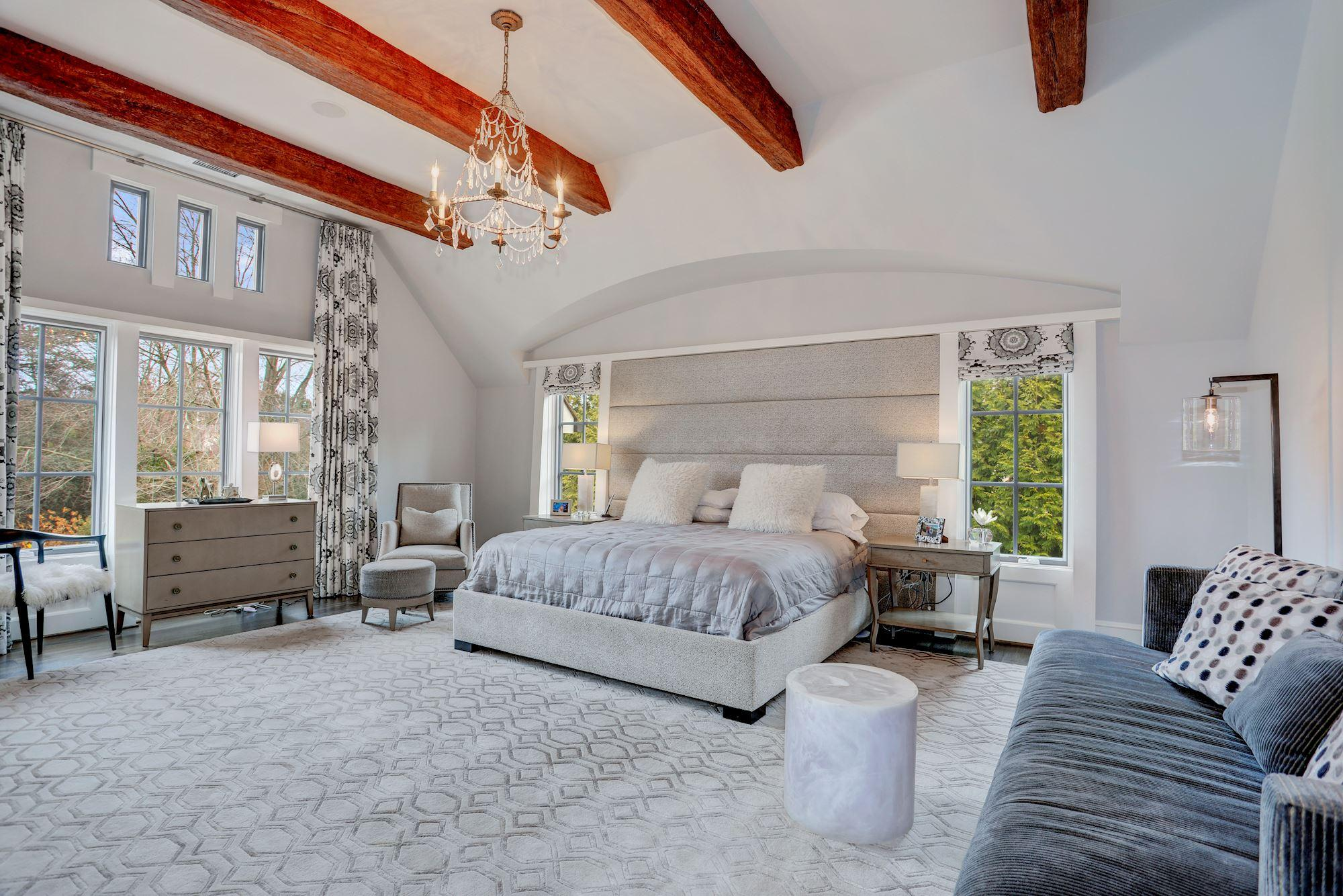 The upper level features five bedrooms, including the master suite with beamed ceilings (Image: Courtesy HomeVisit)<p></p>