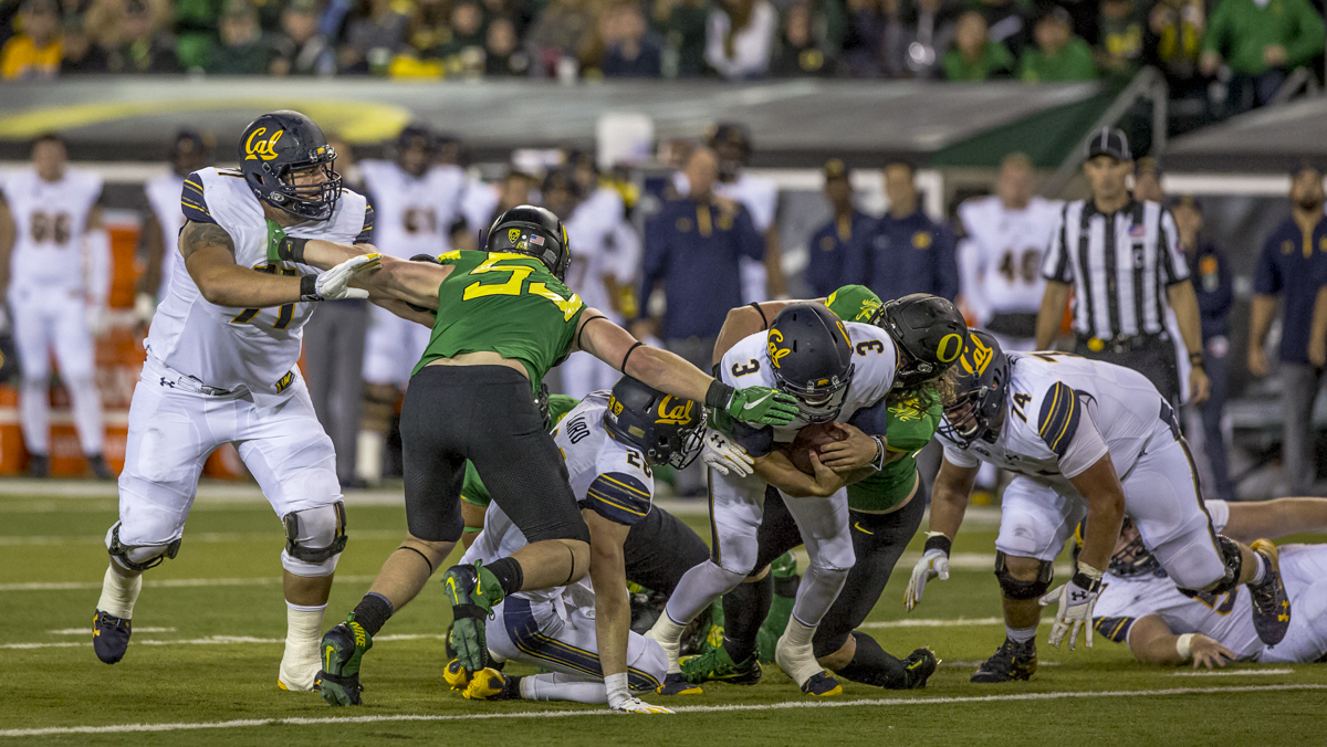 California quarterback Ross Bowers (#3) is brought down by the oregon defense. The Oregon Ducks defeated the California Golden Bears 45 to 24 during an evening game on Saturday September 30, 2017. Photo by Ben Lonergan, Oregon News Lab