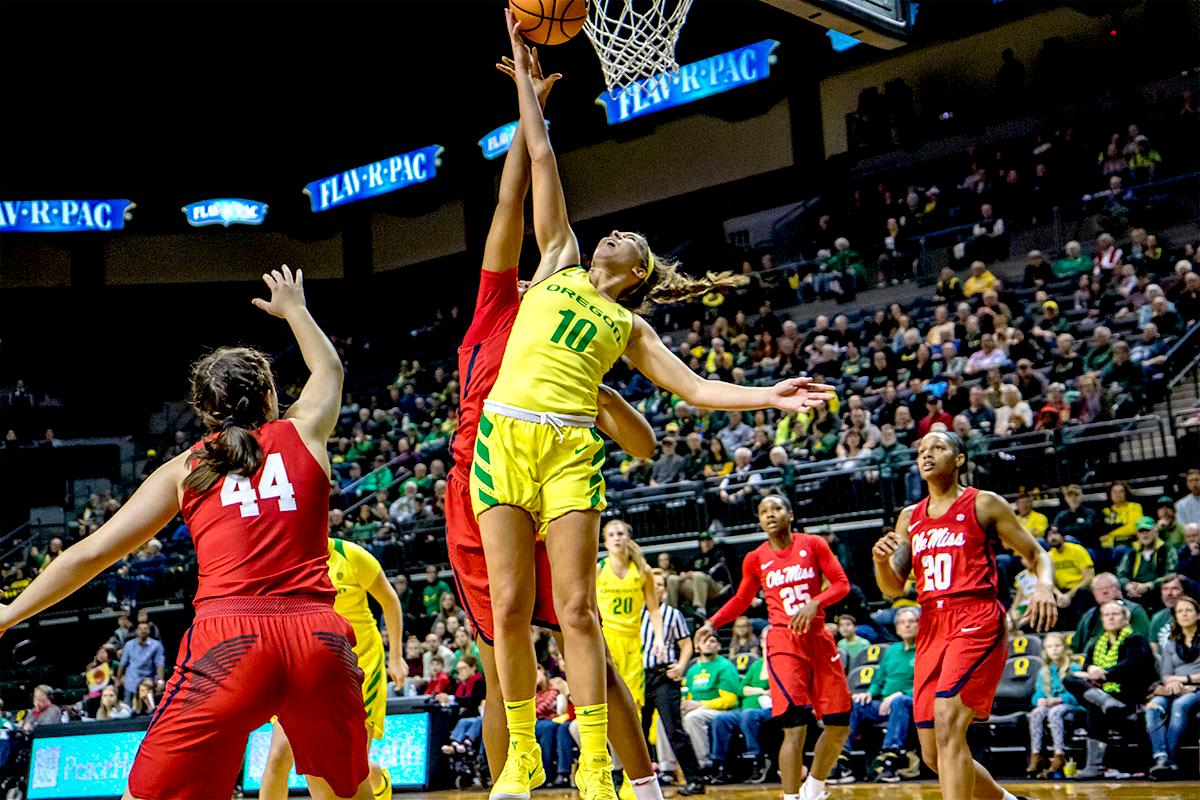 The Duck's Lexi Bando (#10) goes up for the shot. The Duck's Sabrina Ionescu (#20) is introduced at the start of the game against the Ole Miss Rebels. The Oregon Ducks womens basketball team defeated the Ole Miss Rebels 90-46 on Sunday at Matthew Knight Arena. Sabrina Ionescu tied the NCAA record for triple-doubles, finishing the game with 21 points, 14 assists, and 11 rebounds. Ruthy Hebard added 16 points, Satou Sabally added 12, and both Lexi Bando and Maite Cazorla scored 10 each. The Ducks will next face off against Texas A&M on Thursday Dec. 21 and Hawaii on Friday Dec. 22 in Las Vegas for Duel in the Desert before the start of Pac-12 games. Photo by August Frank, Oregon News Lab