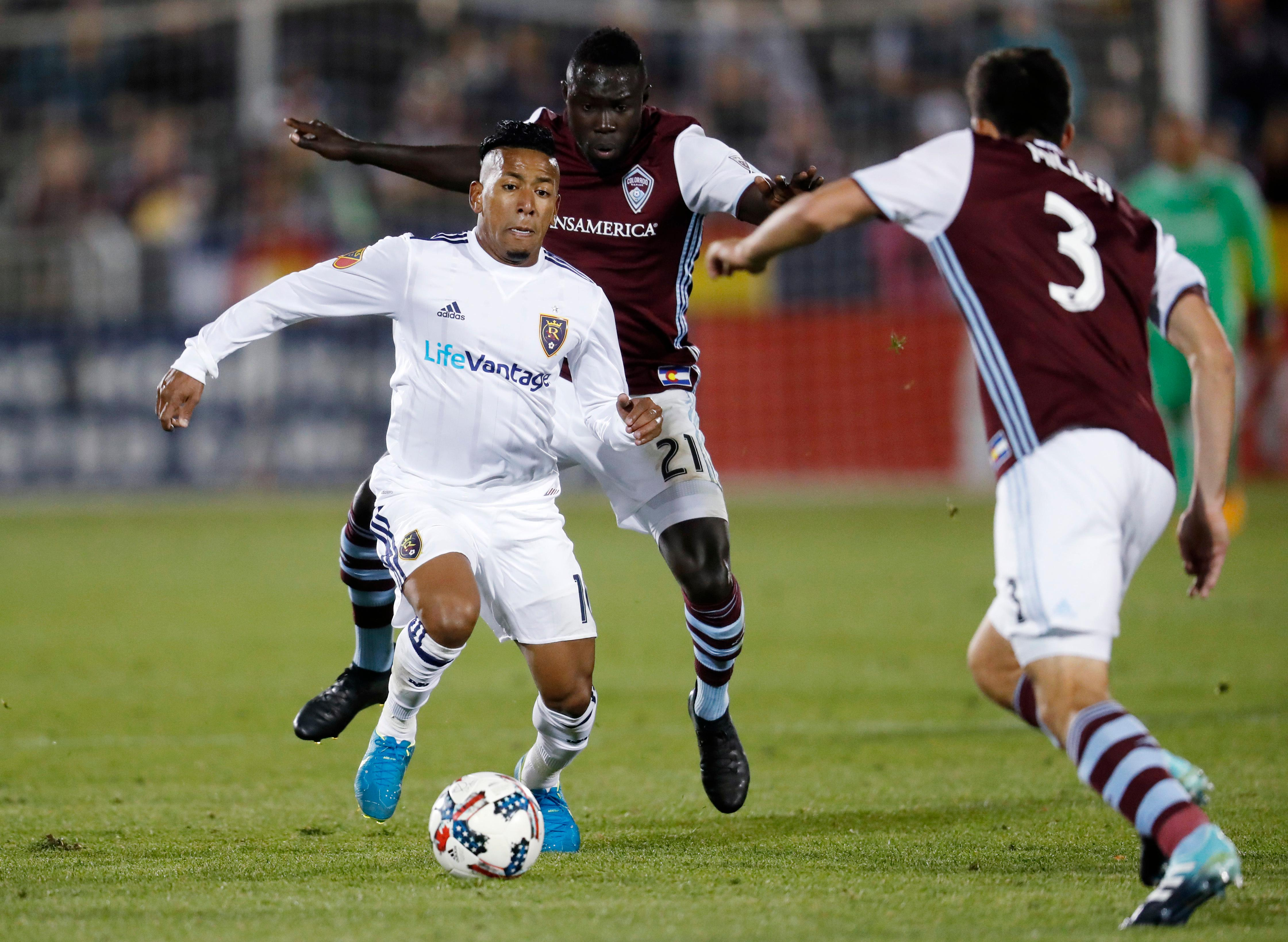 Real Salt Lake forward Joao Plata, front left, drives down the pitch with the ball past Colorado Rapids defender Bismark Adjei-Boateng, back left, as defender Eric Miller comes in to disrupt the play in the second half of an MLS soccer match Sunday, Oct. 15, 2017, in Commerce City, Colo. The Rapids won 1-0. (AP Photo/David Zalubowski)