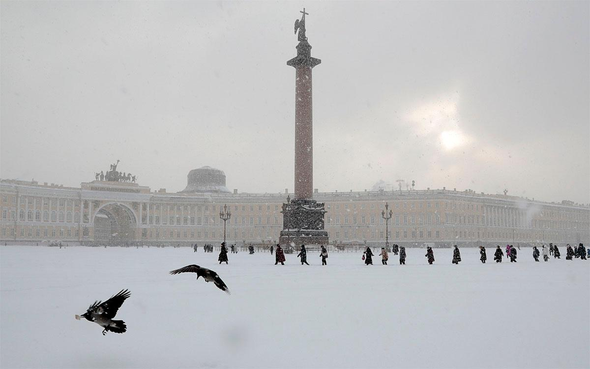 People walk in the snow across Dvortsovaya (Palace) Square in St. Petersburg, Russia, Tuesday, Nov. 8, 2016. Low temperatures caused two days of snowfall in St. Petersburg. (AP Photo/Dmitri Lovetsky)