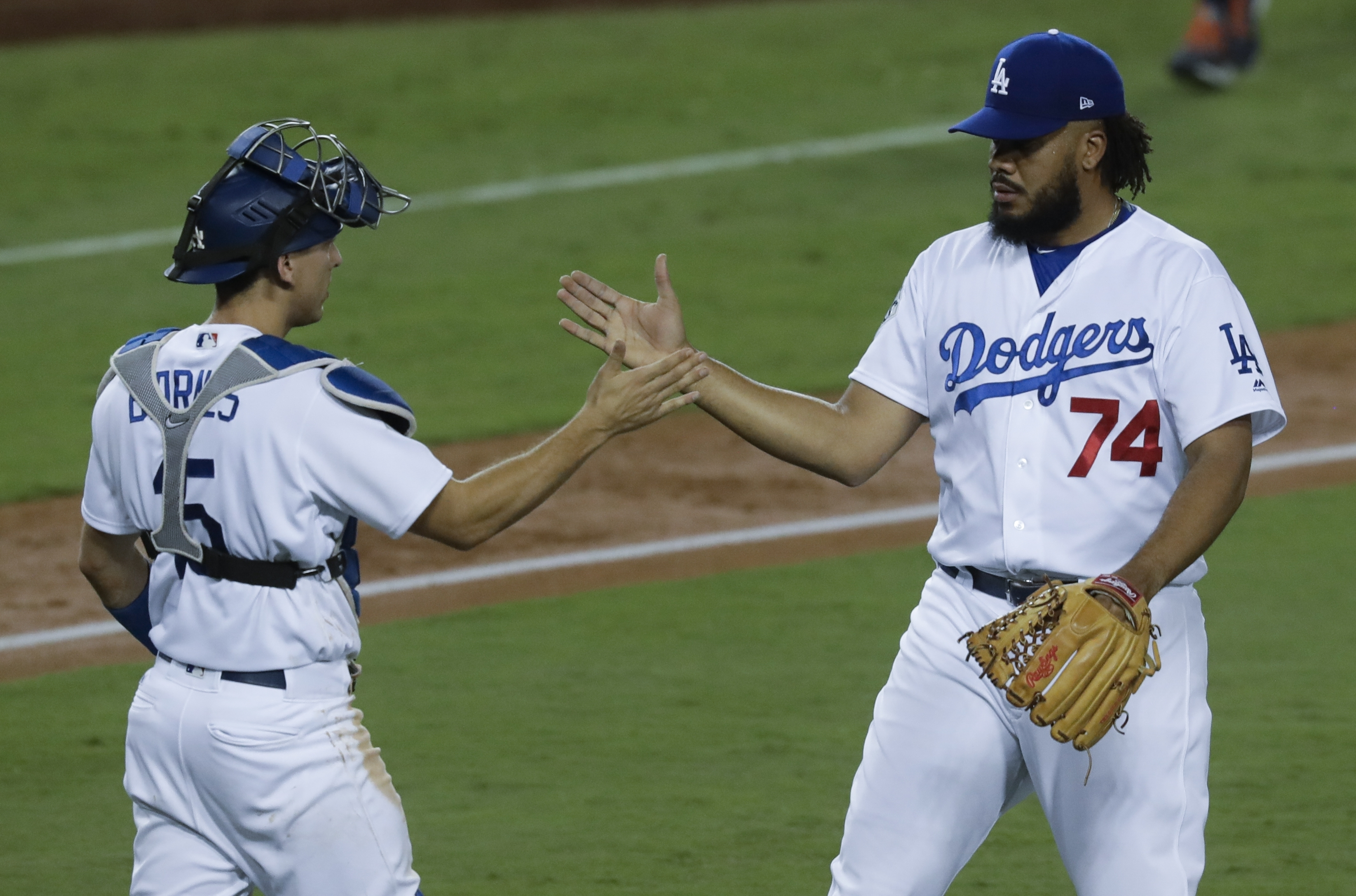 Los Angeles Dodgers' Austin Barnes and Kenley Jansen celebrate after Game 1 of baseball's World Series against the Houston Astros Tuesday, Oct. 24, 2017, in Los Angeles. The Dodgers won 3-1 to take a 1-0 lead in the series. (AP Photo/Alex Gallardo)