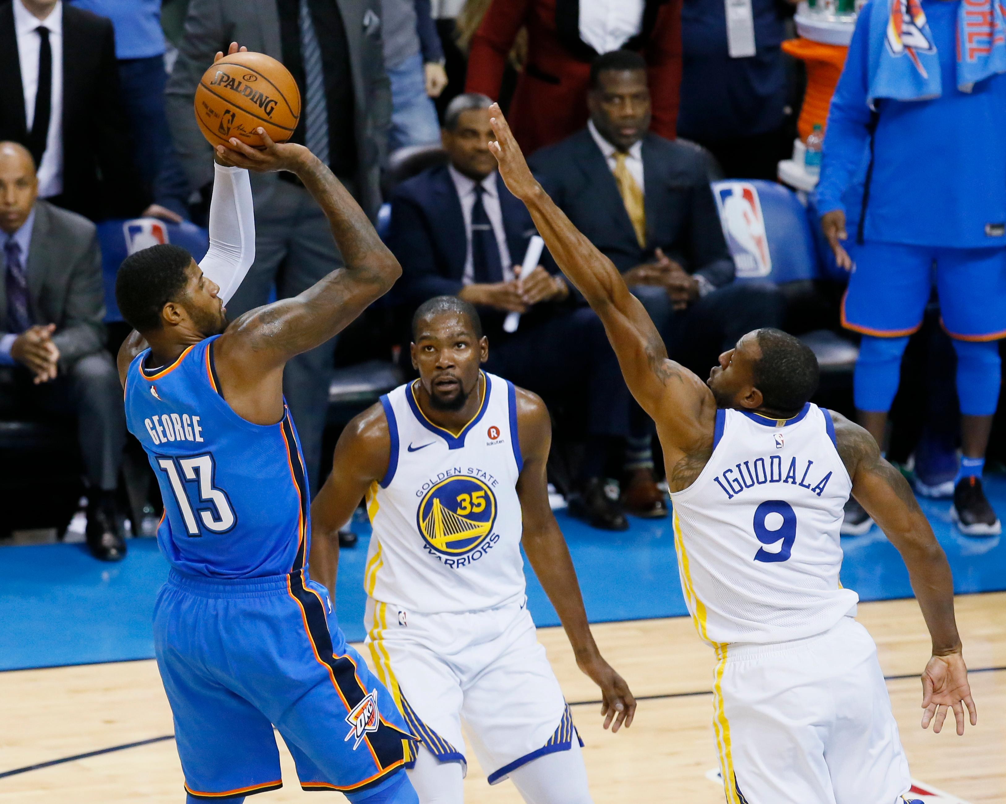Oklahoma City Thunder forward Paul George (13) shoots over Golden State Warriors forward Kevin Durant (35) and forward Andre Iguodala (9) during the second quarter of an NBA basketball game in Oklahoma City, Wednesday, Nov. 22, 2017. (AP Photo/Sue Ogrocki)