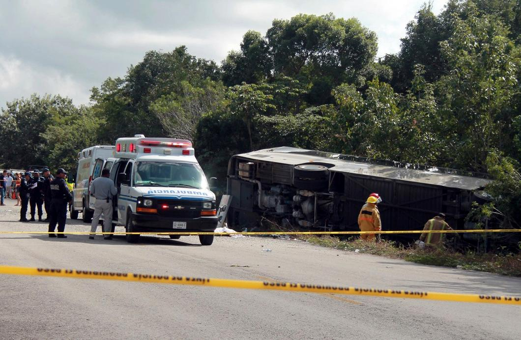 An ambulance sits parked next to an overturned bus in Mahahual, Quintana Roo state, Mexico, Tuesday, Dec. 19, 2017. (Novedades de Quintana Roo via AP)