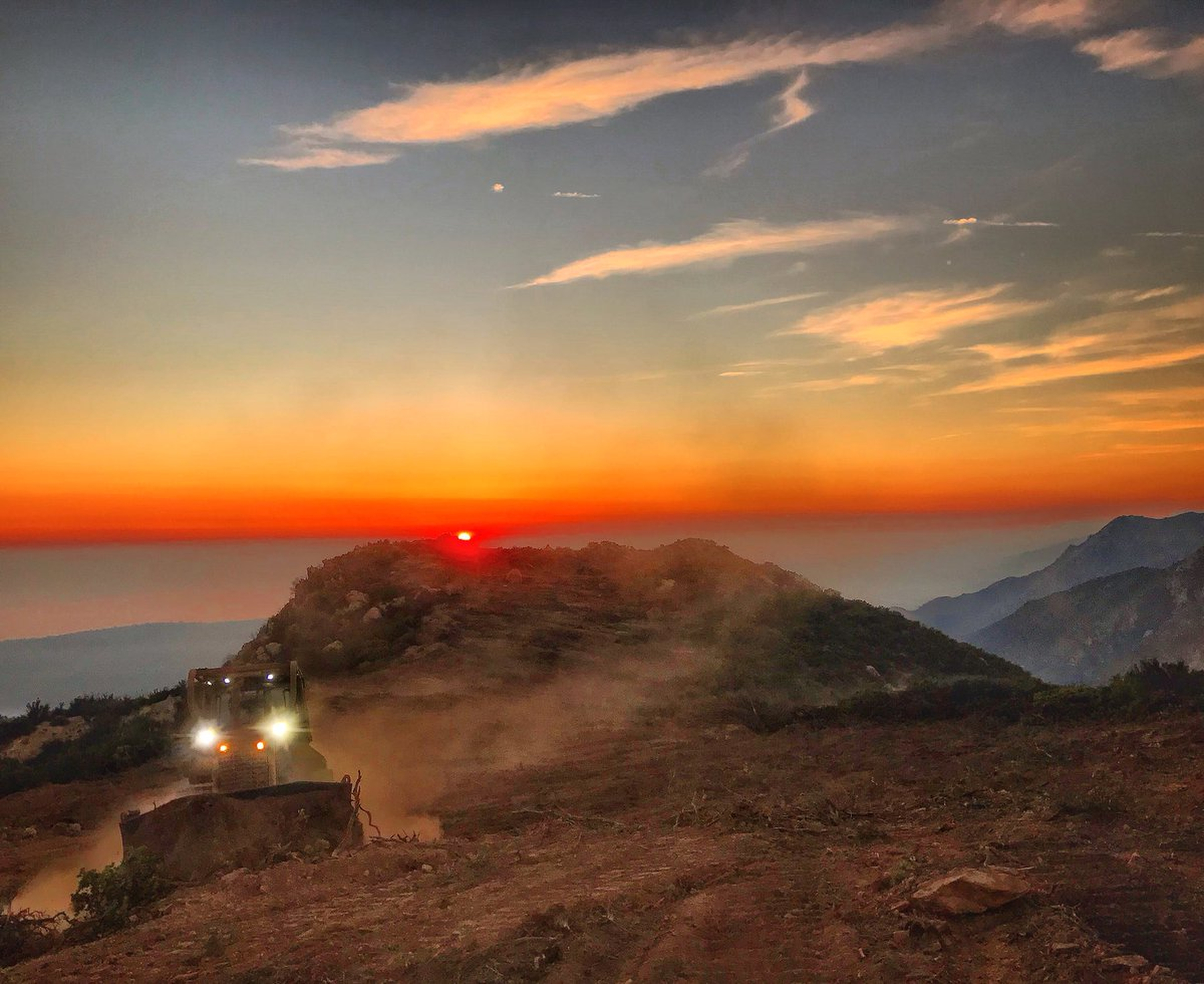 In this photo released by Santa Barbara County Fire Department, a dozer from the Santa Barbara County Fire Department clears a fire break across a canyon from atop Camino Cielo down to Gibraltar to make a stand should the fire move in that direction, Wednesday, Dec. 13, 2017, in the Santa Ynez Mountains area of Santa Barbara, Calif. State fire officials predicted Wednesday night that the Thomas Fire northwest of Los Angeles will continue to grow as it eats up parched brush and hot, dry weather continues. (Mike Eliason/Santa Barbara County Fire Department via AP)