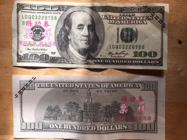 The bills have foreign pink characters printed on the front and back as well as black lines across a corner. (Photo credit: Tryon Police)