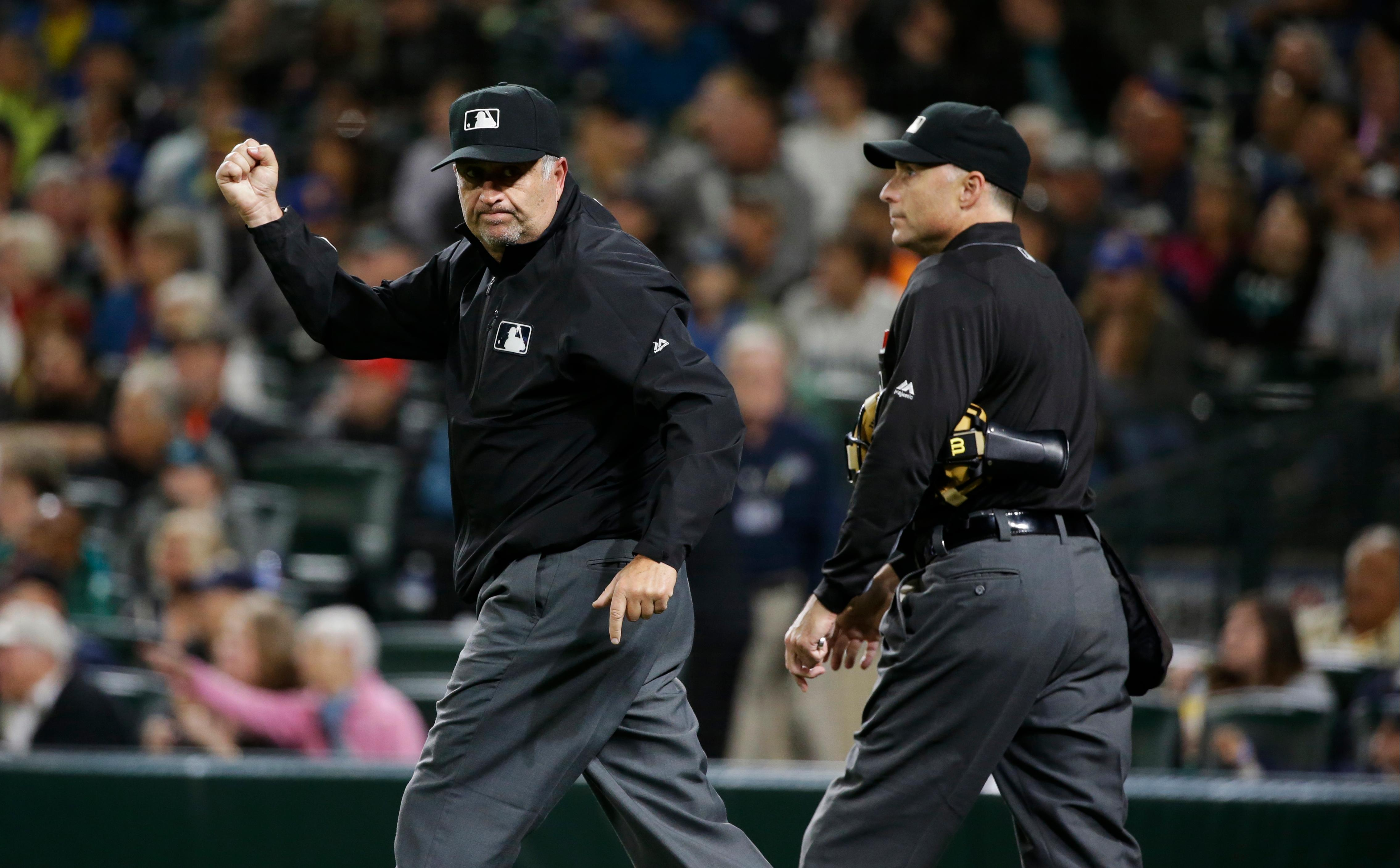 FILE - In this Sept. 8, 2016, file photo, first base umpire Dale Scott, left, signals an out next to home plate umpire Dan Iassogna, right, during a baseball game between the Seattle Mariners and the Texas Rangers in Seattle. Rather than risk yet another concussion, Scott has decided to retire at 58. The veteran crew chief missed nearly the entire 2017 season after a foul ball off the bat of Baltimore slugger Mark Trumbo in Toronto on April 14, caught him hard in the mask, causing Scott's second concussion in nine months and fourth in five years. (AP Photo/Ted S. Warren, File)