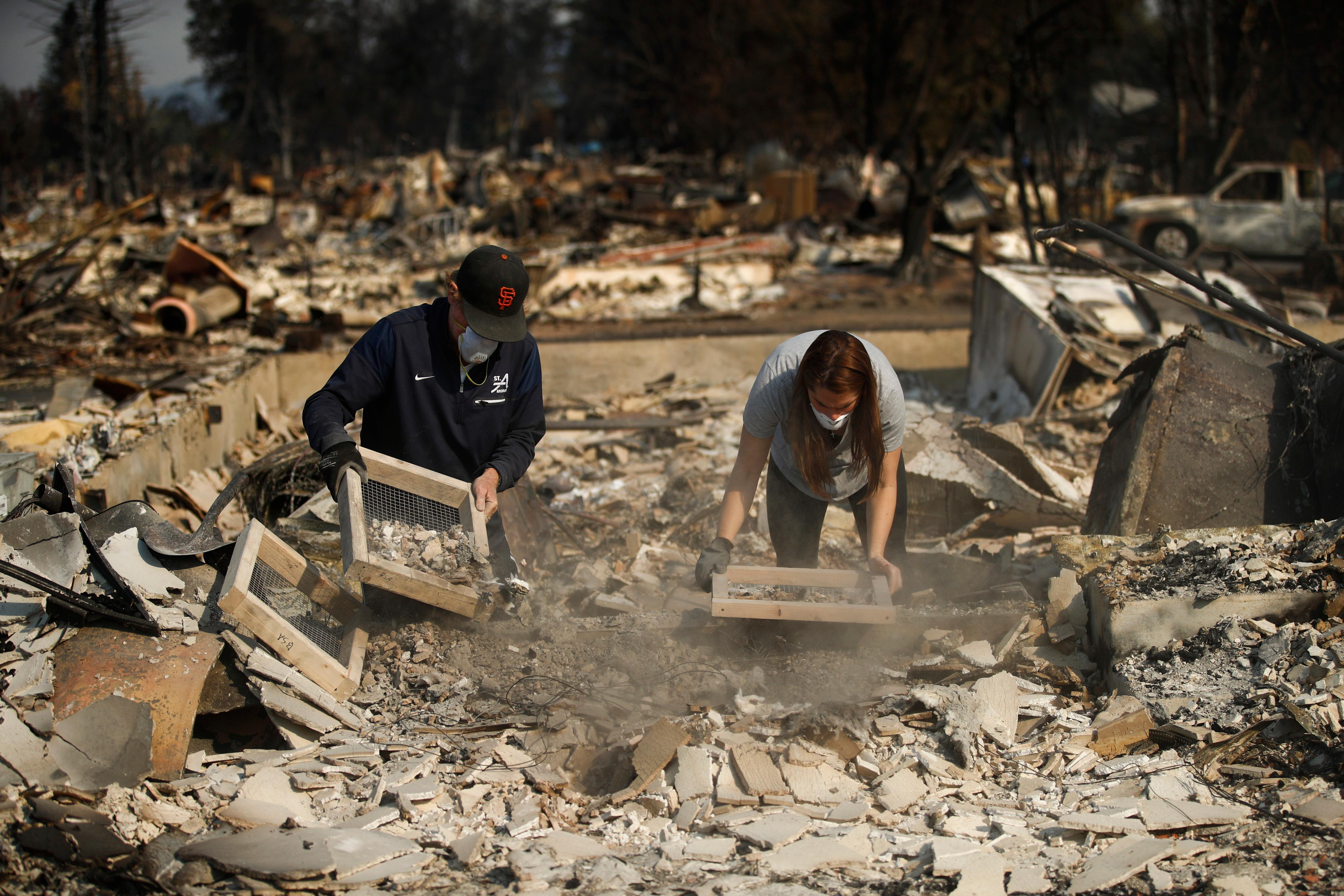 "Ed Curzon, left, and his daughter, Margaret, sift debris to salvage anything they can from the rubbles of their home that was destroyed by a wildfire in the Coffey Park neighborhood Sunday, Oct. 15, 2017, in Santa Rosa, Calif. ""This is our home. This is where we grew up. This is where our kids grew up,"" said Curzon. ""We will rebuild here."" (AP Photo/Jae C. Hong)"