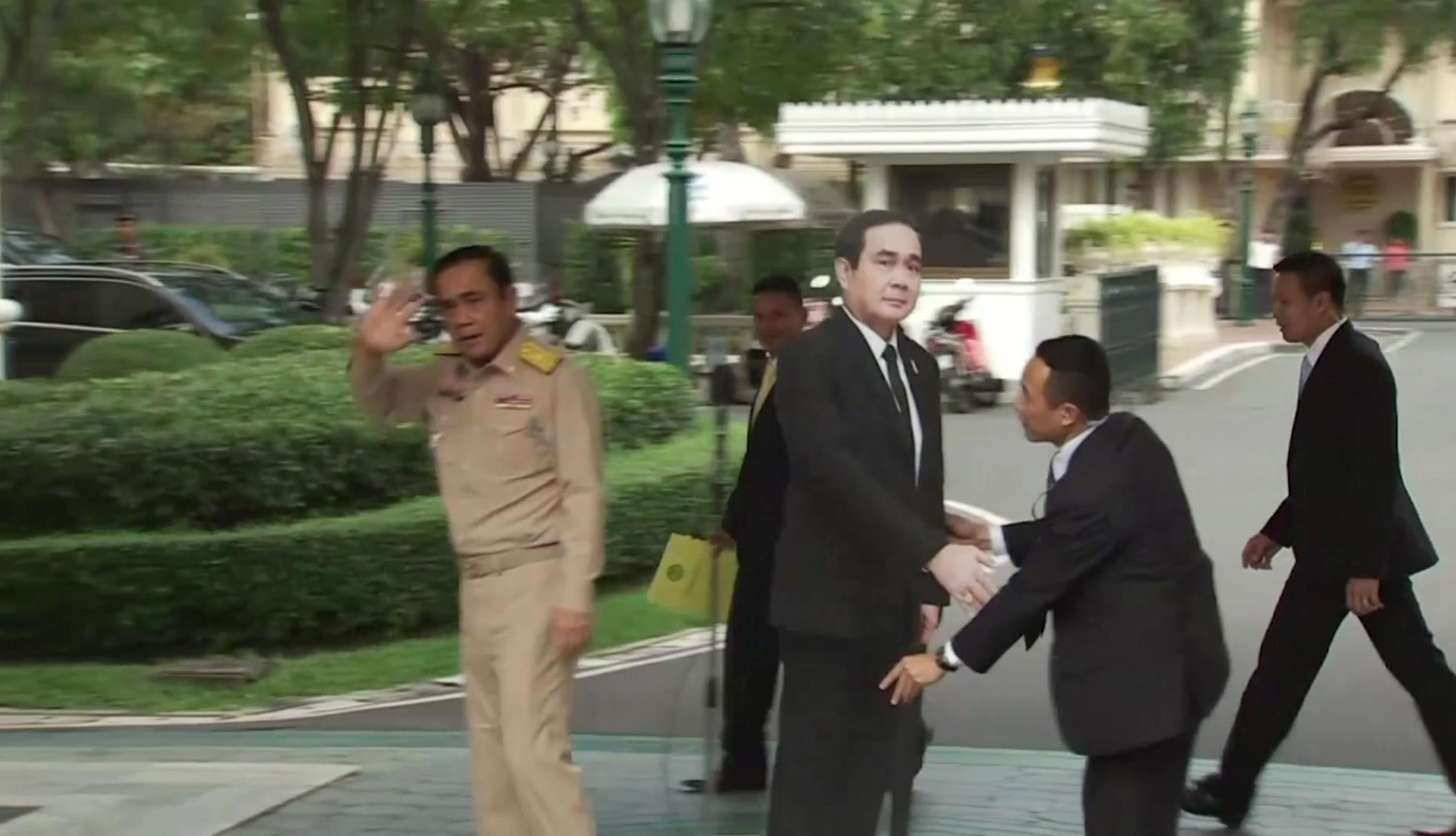 In this image from video, Thailand's Prime Minister Prayuth Chan-ocha, left, waves and walks off as a life-sized cardboard cut-out figure of himself is placed next to the microphone during a media conference in Bangkok, Thailand, Monday Jan. 8, 2018. (TPBS via AP)<p></p>