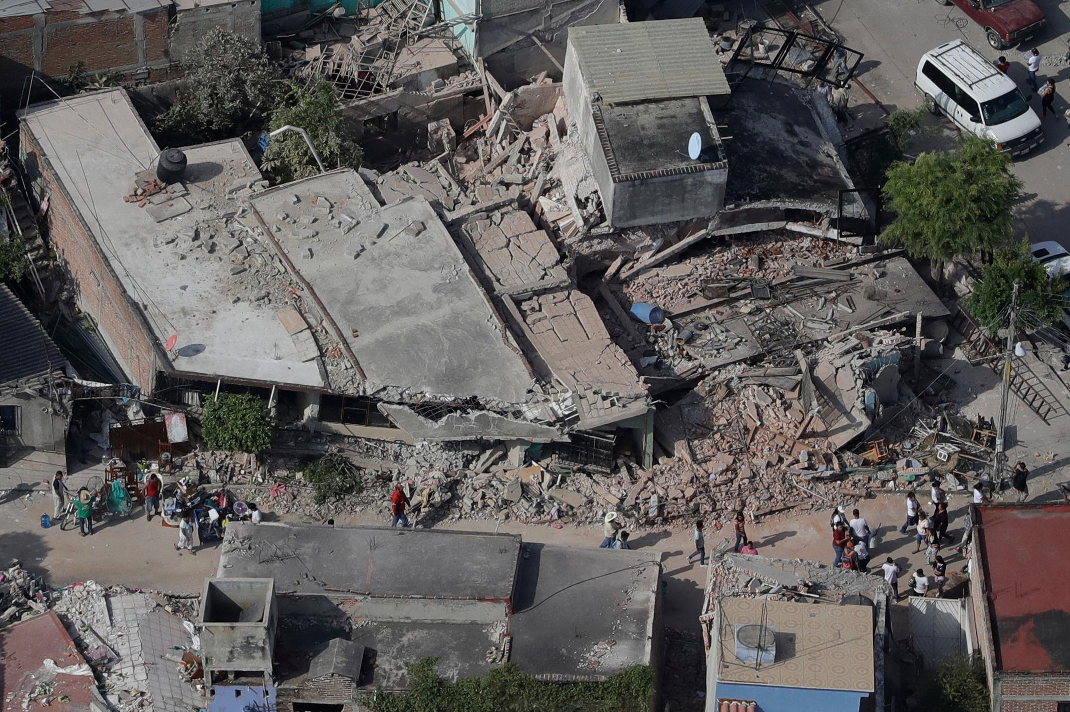 People walk through a neighborhood where many buildings collapsed a day before, during a magnitude 7.1 earthquake in Jojutla, Mexico, Wednesday, Sept. 20, 2017. Police, firefighters and civilians are digging frantically through the rubble of collapsed schools, homes and apartment buildings looking for survivors. (AP Photo/Rebecca Blackwell)