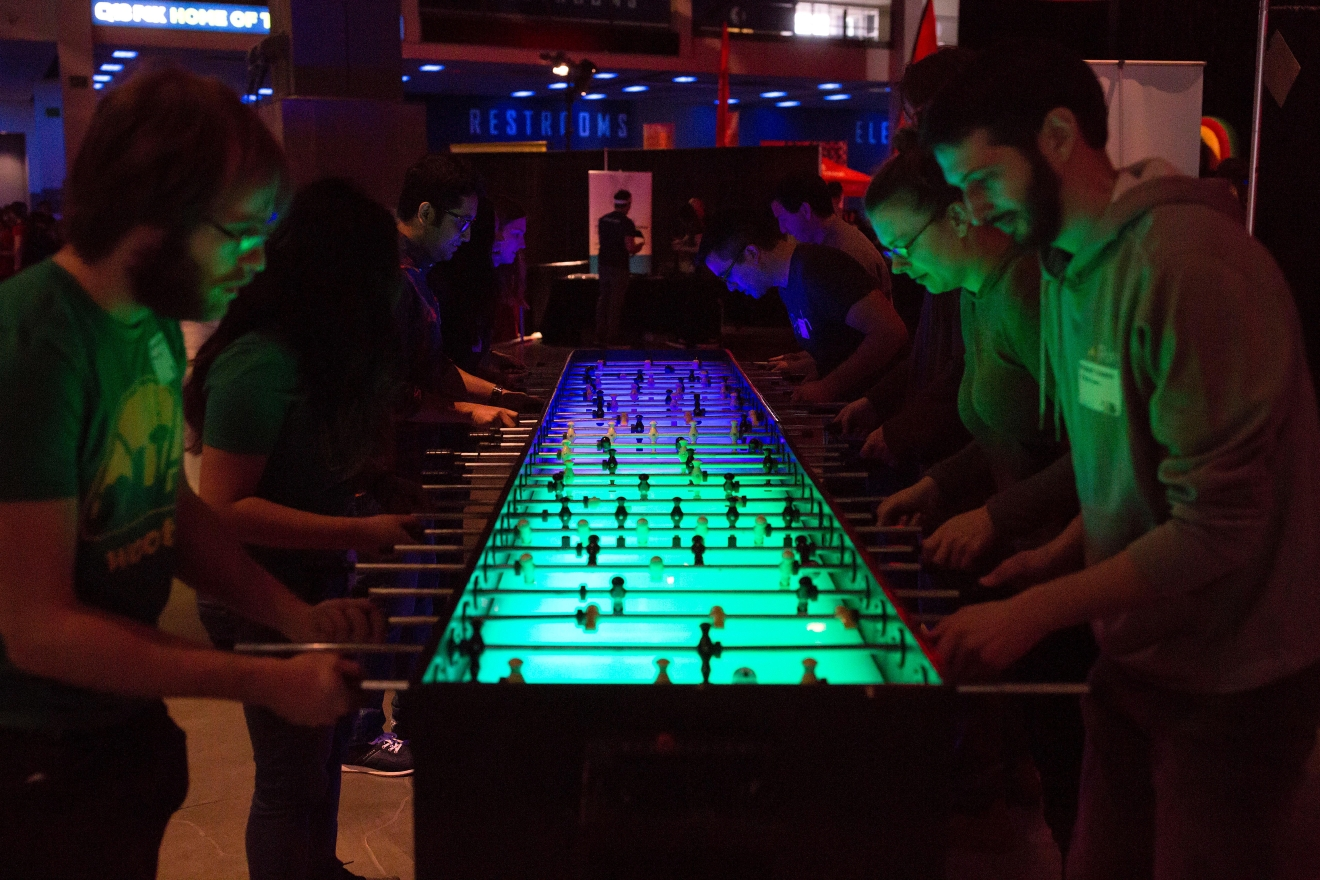 Participants compete in a game of foosball on an extra-long table at the 6th annual Geekwire Bash at the CenturyLink Event Center. (Sy Bean / Seattle Refined)
