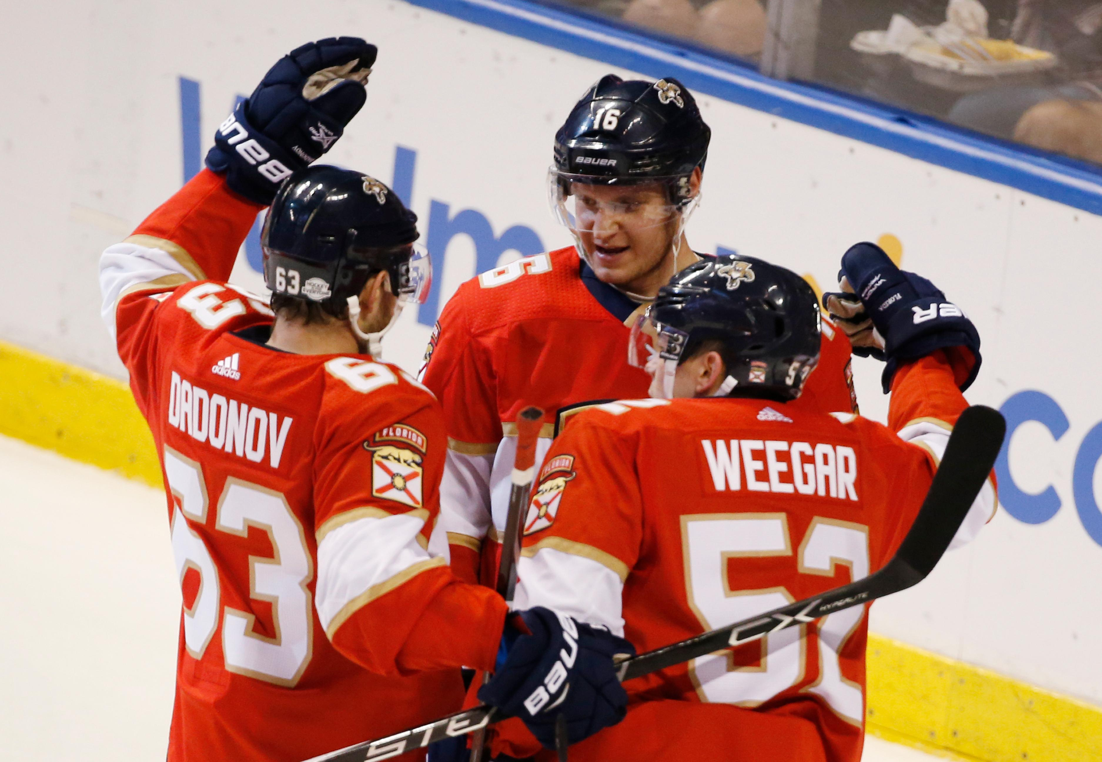 Florida Panthers right wing Evgenii Dadonov (63) and defenseman MacKenzie Weegar (52) congratulate center Aleksander Barkov (16) after Barkov scored a goal during the second period of an NHL hockey game against the Detroit Red Wings, Saturday, Feb. 3, 2018 in Sunrise, Fla. (AP Photo/Wilfredo Lee)