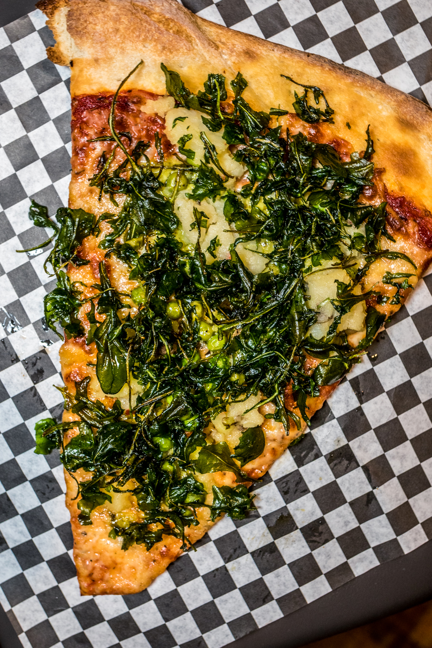 A slice of the veggie pizza of the day: pea pesto, peas, mashed potato, onion, and crispy kale / Image: Catherine Viox{ }// Published: 12.26.19
