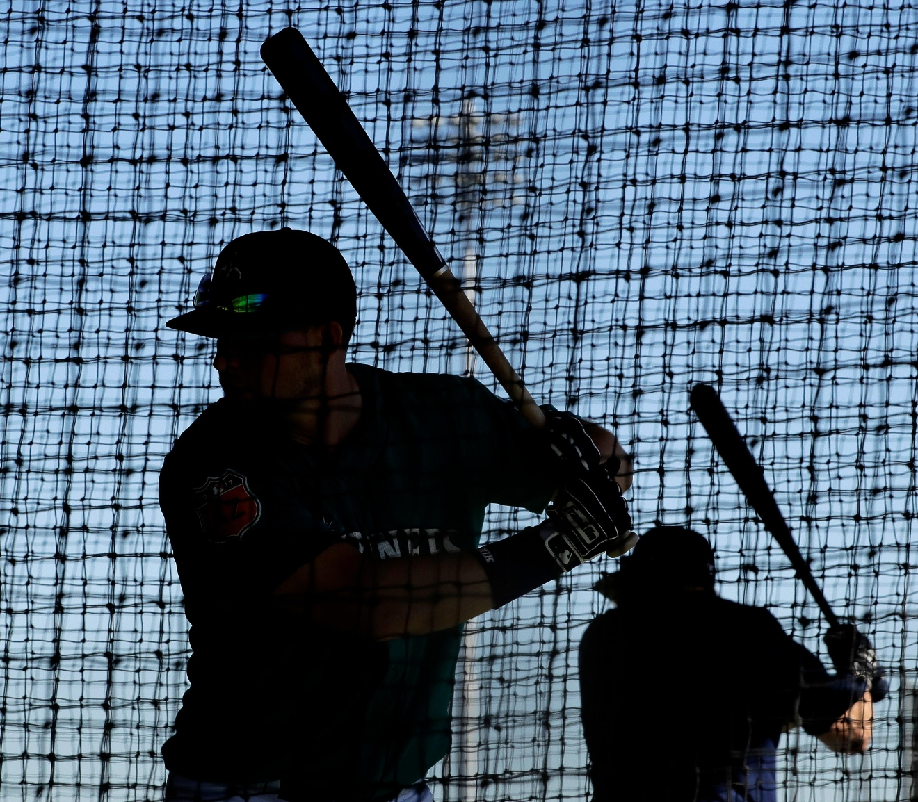 Players for the Seattle Mariners practice in a batting cage during baseball spring training Tuesday, Feb. 21, 2017, in Peoria, Ariz. (AP Photo/Charlie Riedel)