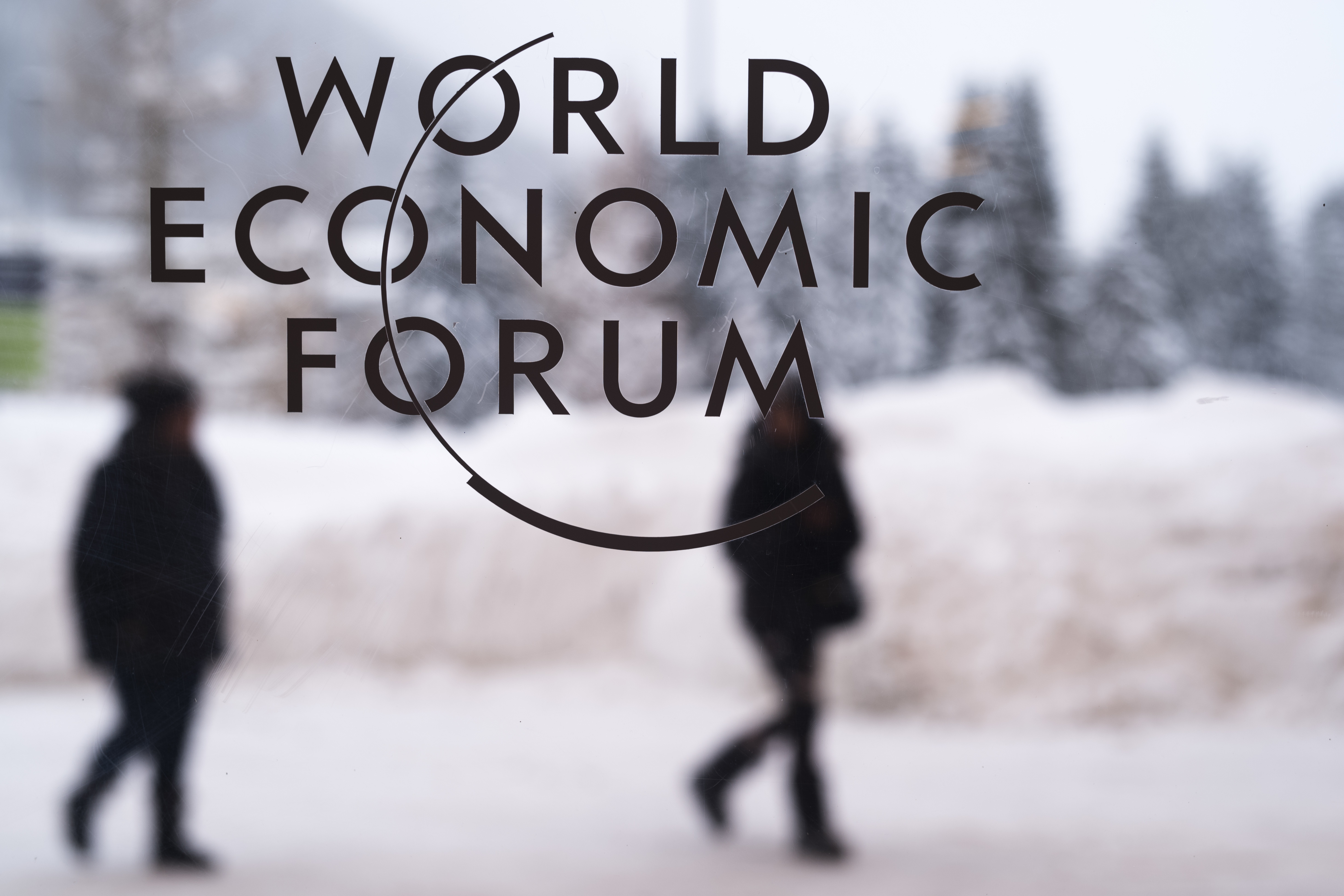 Two persons walk behind the logo of the World Economic Forum at the meeting's conference center in Davos, Switzerland, Sunday, Jan. 21, 2018. One question looms as President Donald Trump packs his bags and heads for the mountains of Switzerland later this week: How will the diet Coke-loving nationalist fit in with the champagne-swilling globalists he'll encounter at the World Economic Forum in Davos?  (AP Photo/Markus Schreiber)