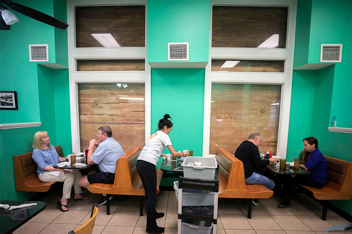 Henry's Restaurant manager Nhi Brayman, center, cleans a table while customers eat breakfast behind boarded up windows, Sunday, Sept., 10, 2017, in downtown Savannah, Ga. Hurricane Irma is expected effect parts of Georgia as early as Sunday night. (AP Photo/Stephen B. Morton)