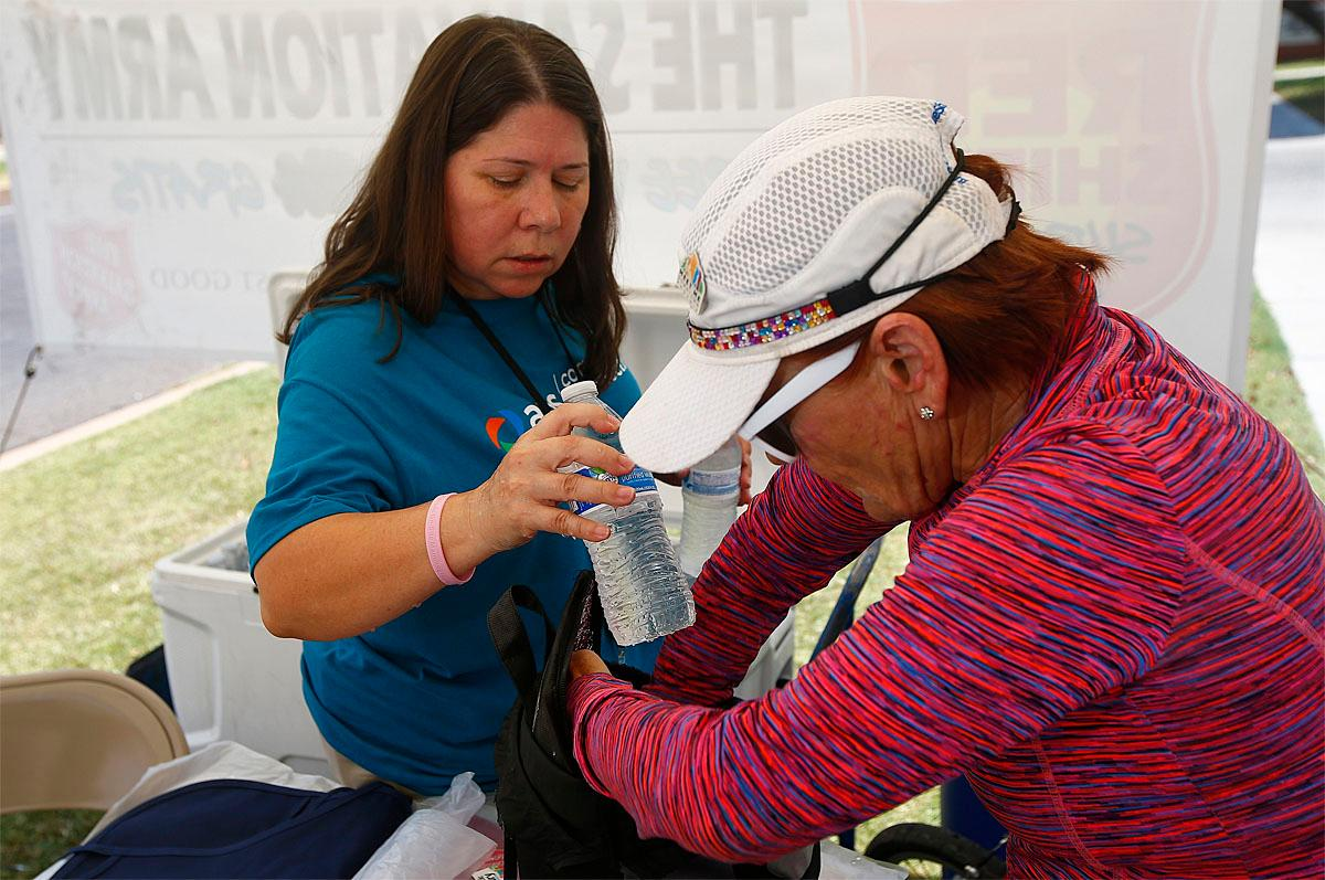 Salvation Army volunteer Evangeline Ford, left, helps Dianne Barker, right, load up her bag with water as people try to keep hydrated and stay cool as temperatures climb to near-record highs, Monday, June 19, 2017, in Phoenix. (AP Photo/Ross D. Franklin)