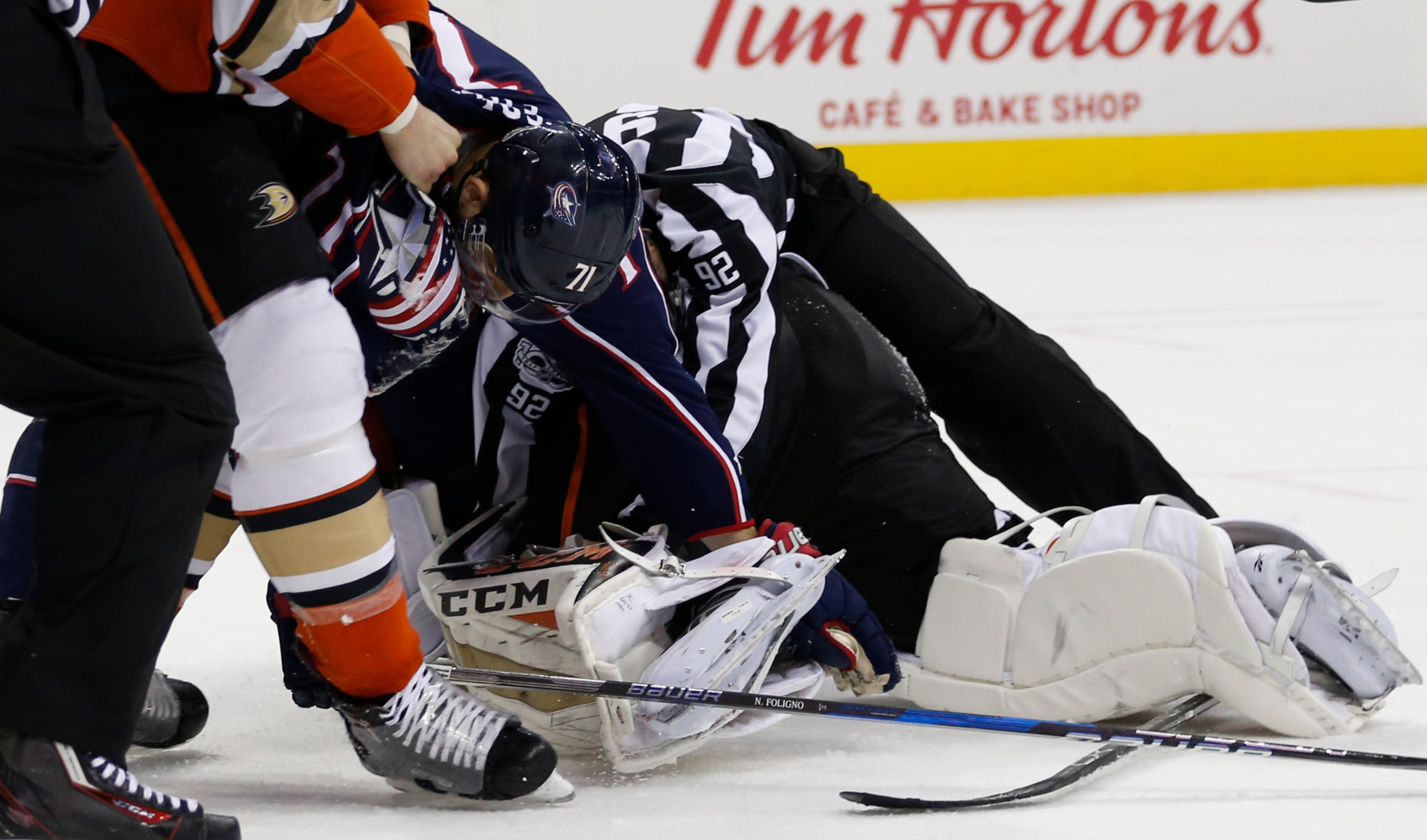 A referee tries to separate Columbus Blue Jackets' Nick Foligno (71) and Anaheim Ducks goalie John Gibson after a scuffle during the second period of an NHL hockey game Friday, Dec. 1, 2017, in Columbus, Ohio. (AP Photo/Jay LaPrete)