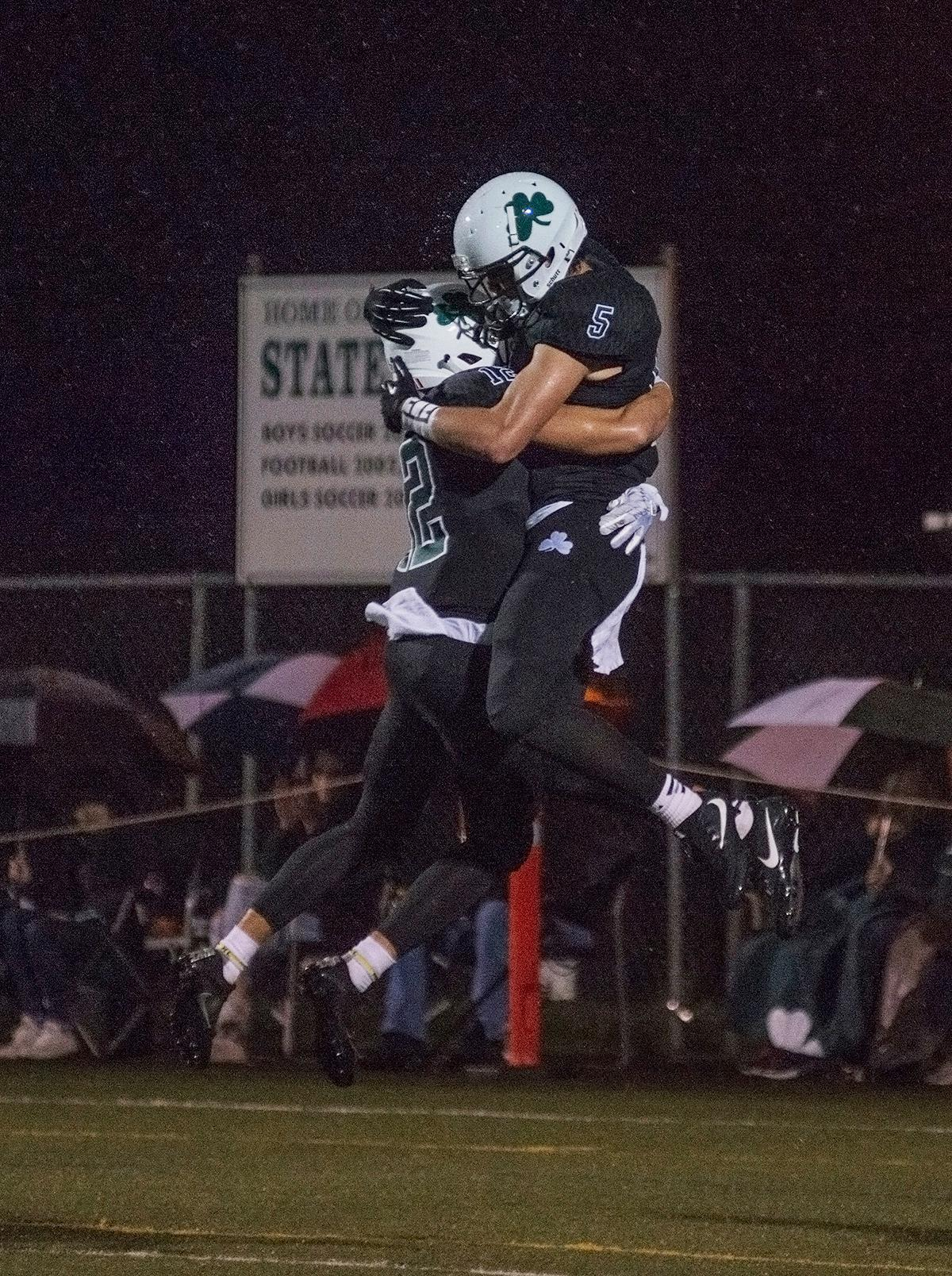 Sheldon Irish wide receivers Patrick Herbert (#5) and Uta Mageo (#12) celebrate a touchdown.  On a rainy Monday evening, Sheldon defeated West Salem 41 to 7 at their home field. The game had been postponed from Friday due to unhealthy levels of smoke in the atmosphere from nearby forest fires. Abigail Winn, Oregon News Lab