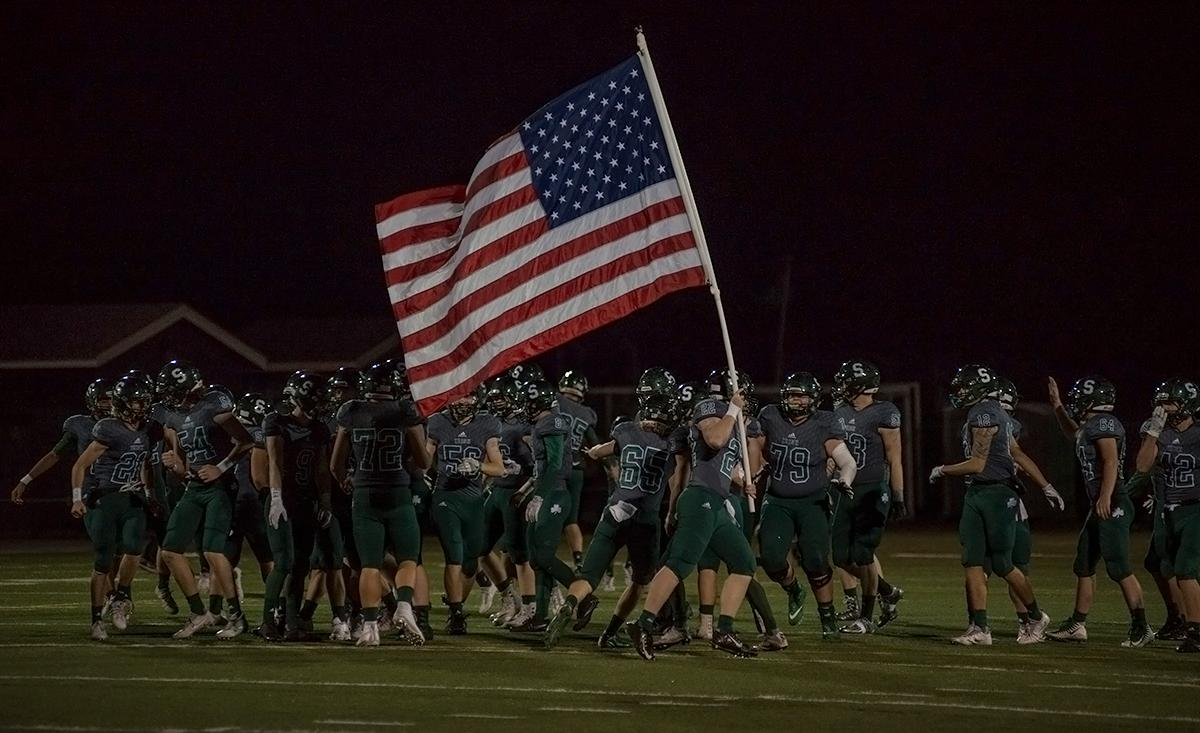Sheldon Irish running back Chris Collins (#22) carries the American flag as the team enters the stadium. The Sheldon Irish defeated the Beaverton Beavers 48-7 on Friday night at Sheldon in the first round of 6A state playoffs. Photo by Abigail Winn, Oregon News Lab