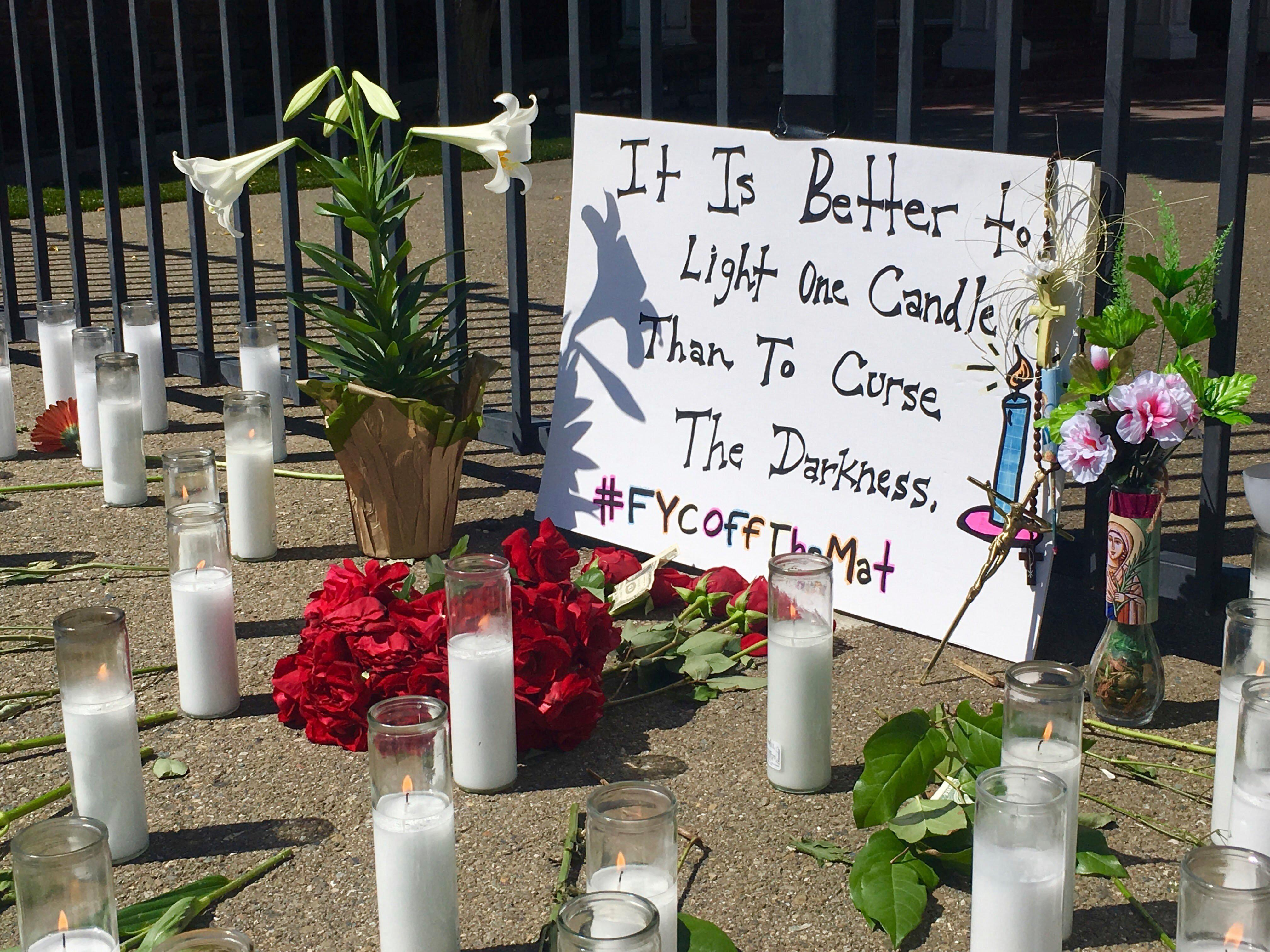 A memorial of candles and flowers honors victims of Tuesday's shooting outside Catholic Charities Wednesday, April 19, 2017 in Fresno, Calif.  Mark Gassett, 37, of Fresno, had just picked up groceries at a Catholic Charities building when he was gunned down. David Jackson, 58, of Fresno, was gunned down in the parking lot of the charity's building.  (Carmen George/The Fresno Bee via AP)