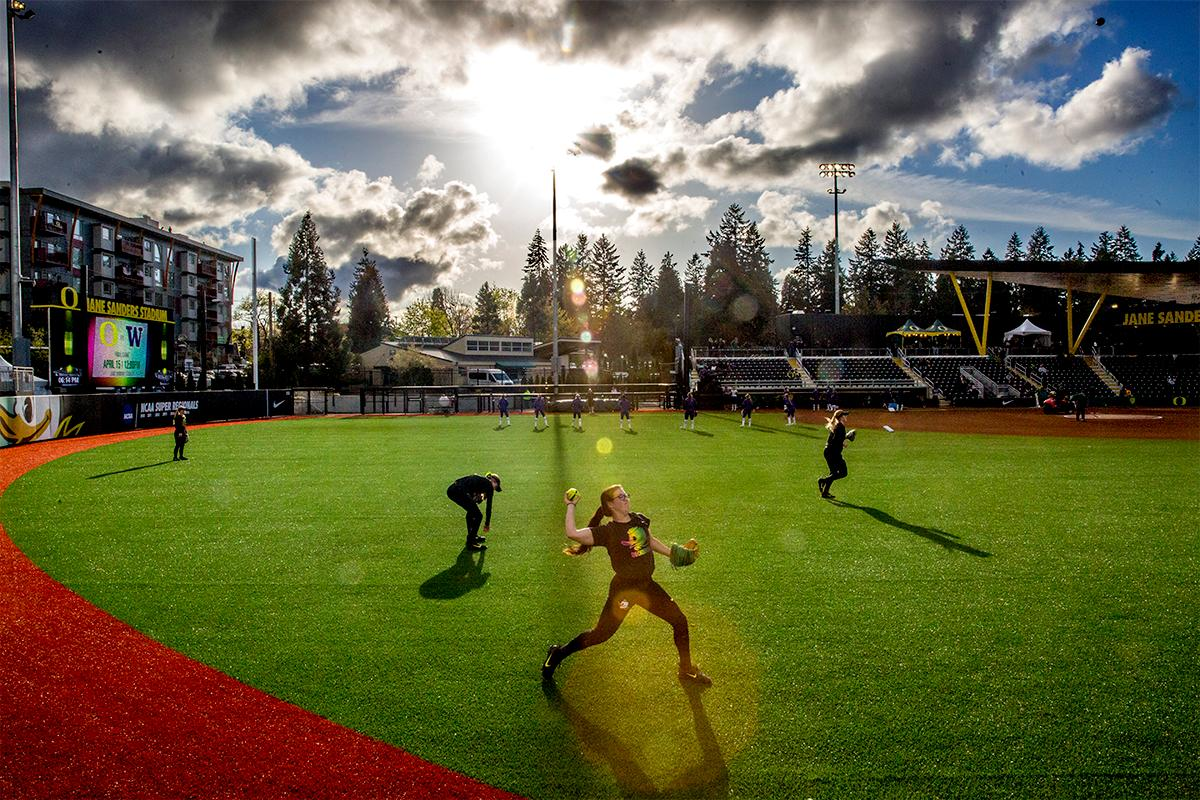 The Duck's team practices under the sunlight before the start of the game. In Game Two of a three-game series, the University of Oregon Ducks softball team defeated the University of Washington Huskies 4-1 Friday night in Jane Sanders Stadium. Danica Mercado (#2), Alexis Mack (#10) and Mia Camuso (#7) all scored in the win, Mack twice. The Ducks play the Huskies for the tie breaker on Saturday with the first pitch at noon. Photo by August Frank, Oregon News Lab