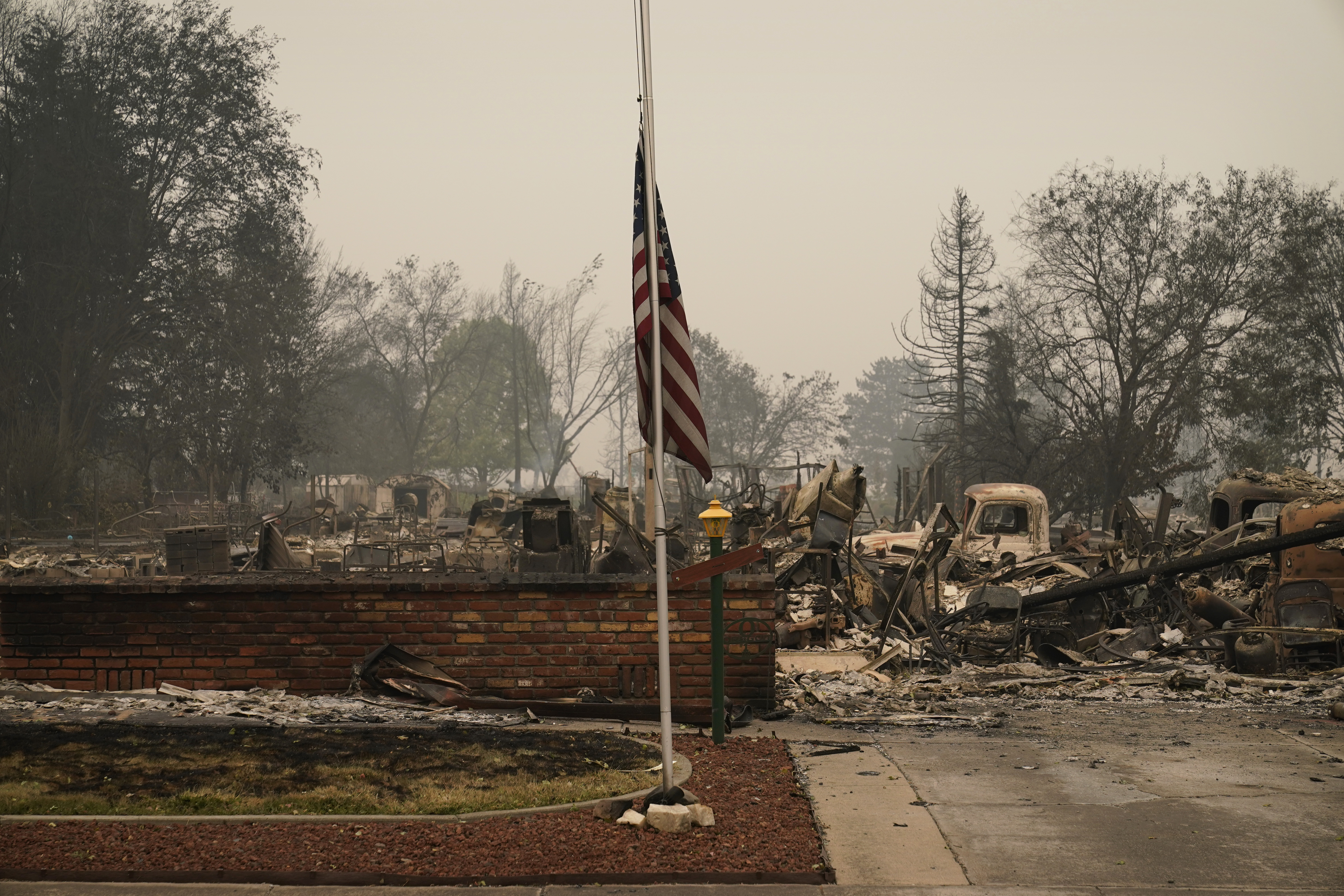 A flag flies in a neighborhood destroyed by the Almeda Fire, Friday, Sept. 11, 2020, in Phoenix, Ore. (AP Photo/John Locher)