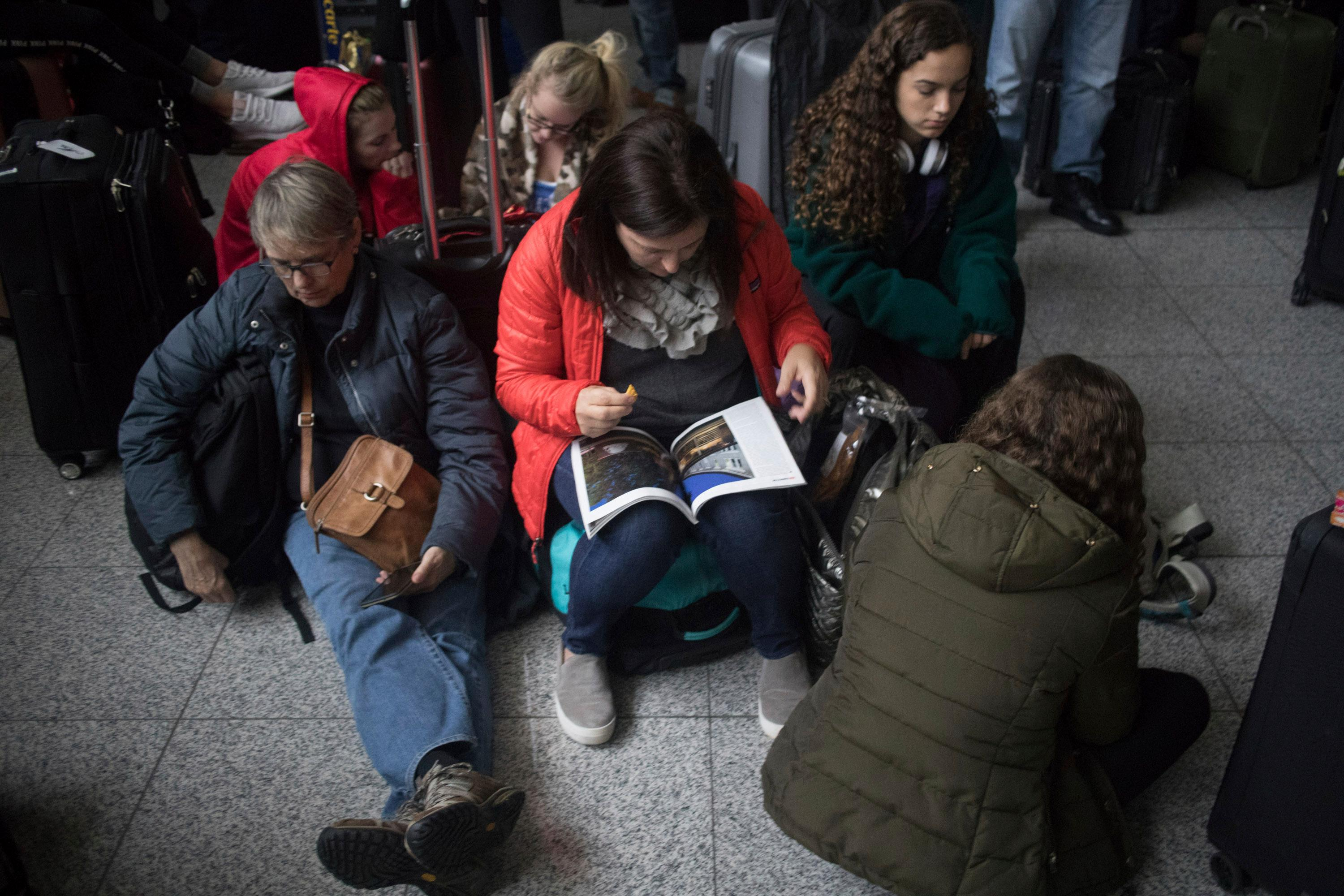 Passengers wait for the lights to come back on at Hartsfield-Jackson International Airport, Sunday, Dec. 17, 2017, in Atlanta. A sudden power outage at the Hartsfield-Jackson Atlanta International Airport on Sunday grounded scores of flights and passengers during one of the busiest travel times of the year. (Steve Schaefer/Atlanta Journal-Constitution via AP)