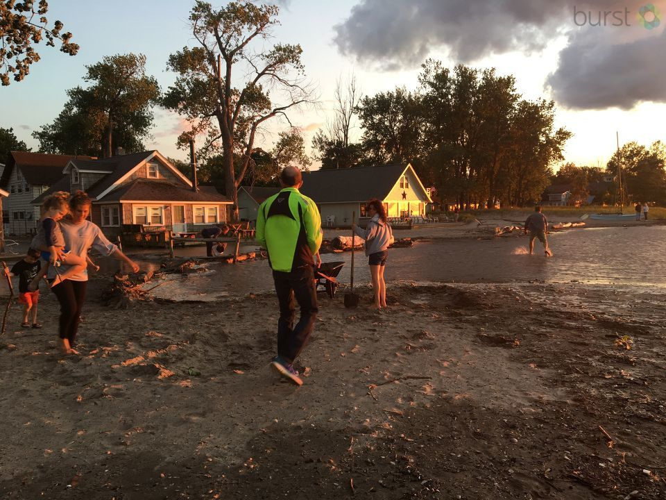 People in the area look on flooded homes in the area after waves cause flooding along the shoreline.
