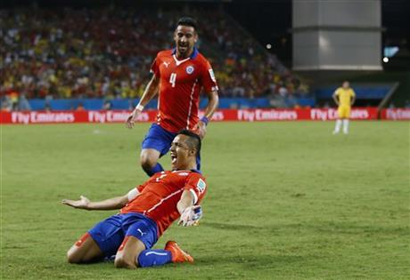 Chile's Mauricio Isla (4) watches as Alexis Sanchez celebrates after scoring his side's first goal during the first half of the group B World Cup soccer match between Chile and Australia in the Arena Pantanal in Brazil.